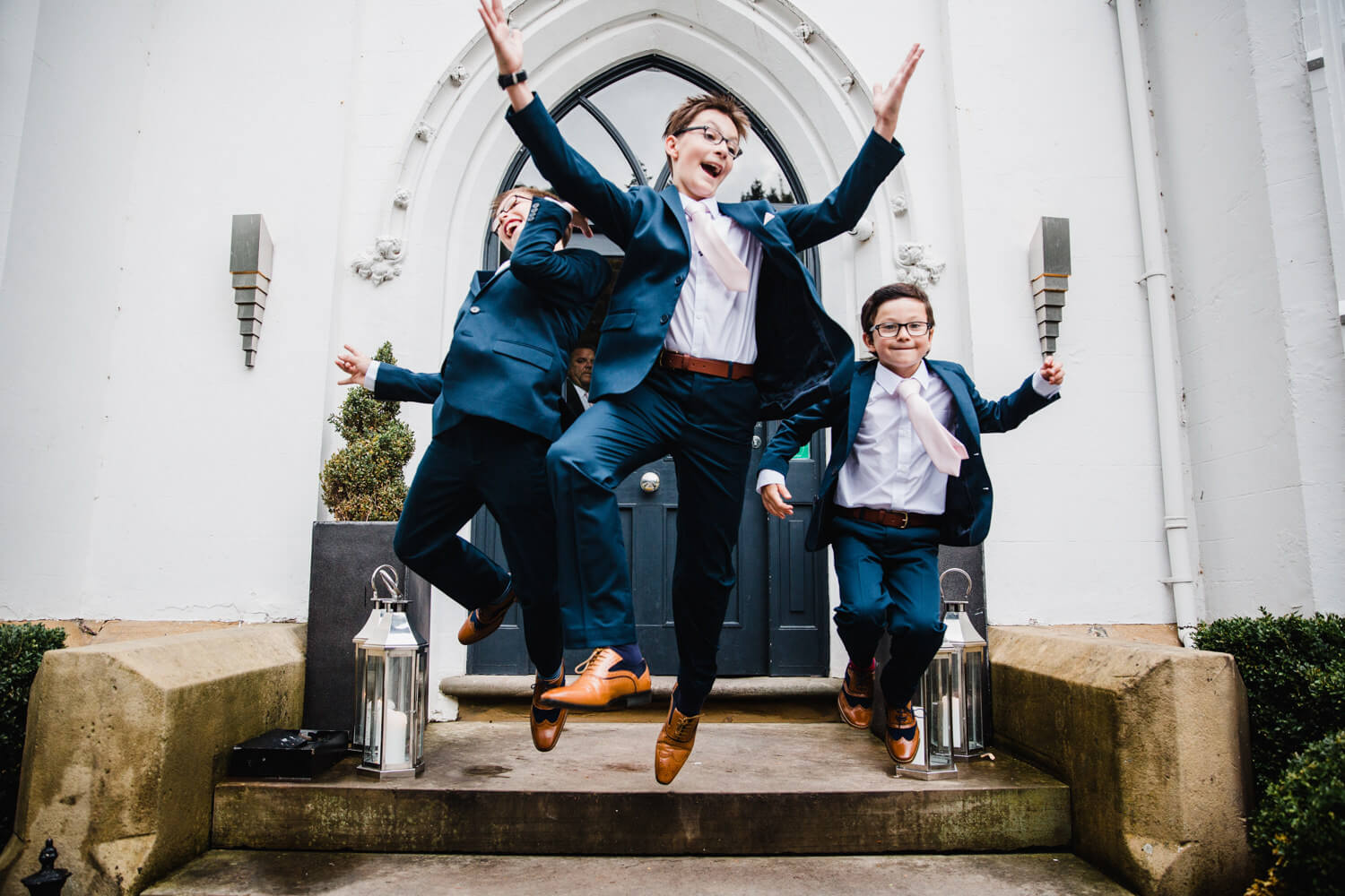 pageboys jumping off step in didsbury house doorway