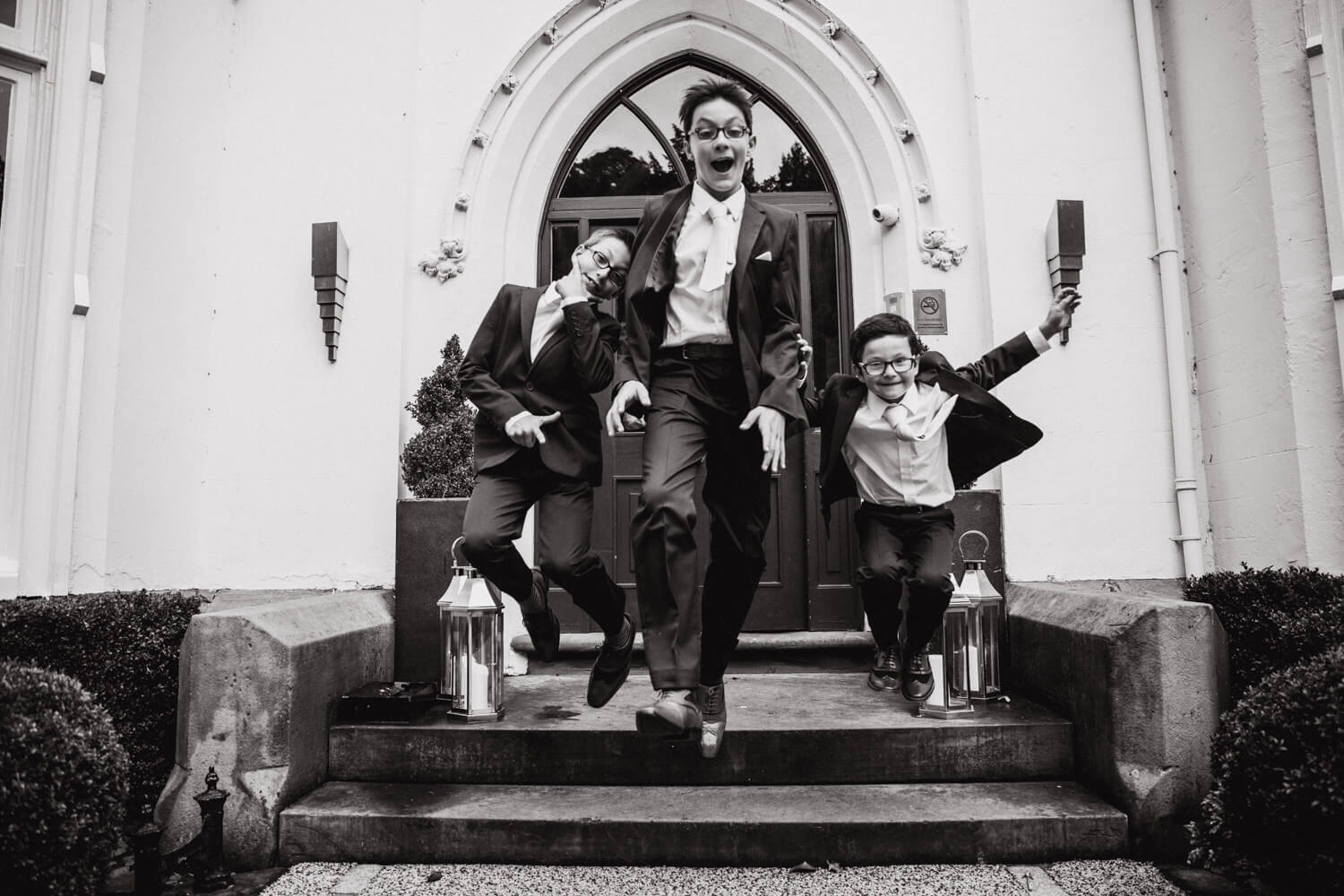 black and white photograph of ushers jumping in entrance to didsbury house hallway