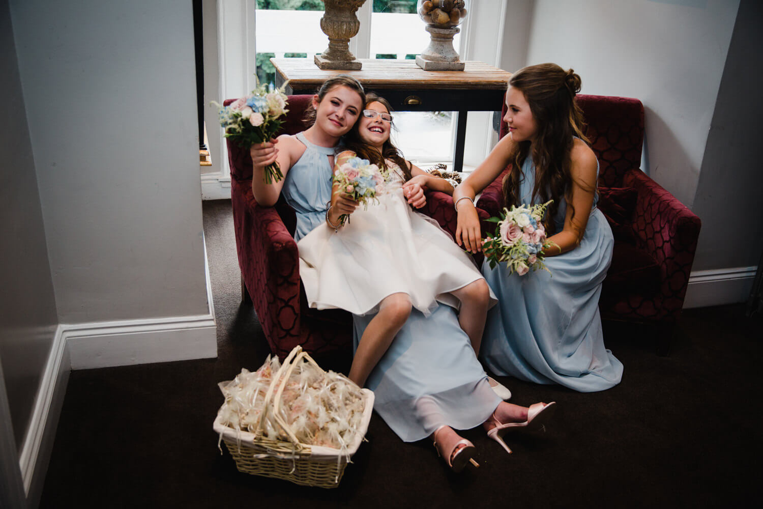 bridesmaids lounge on chairs in hallway
