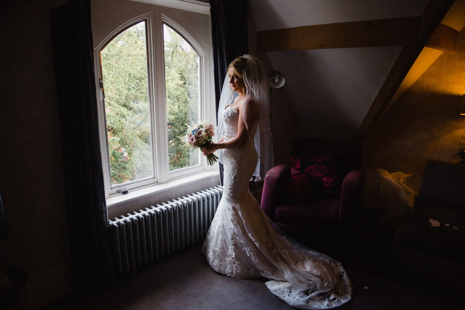portrait photograph of bride in bridal suite window holding bouquet of flowers