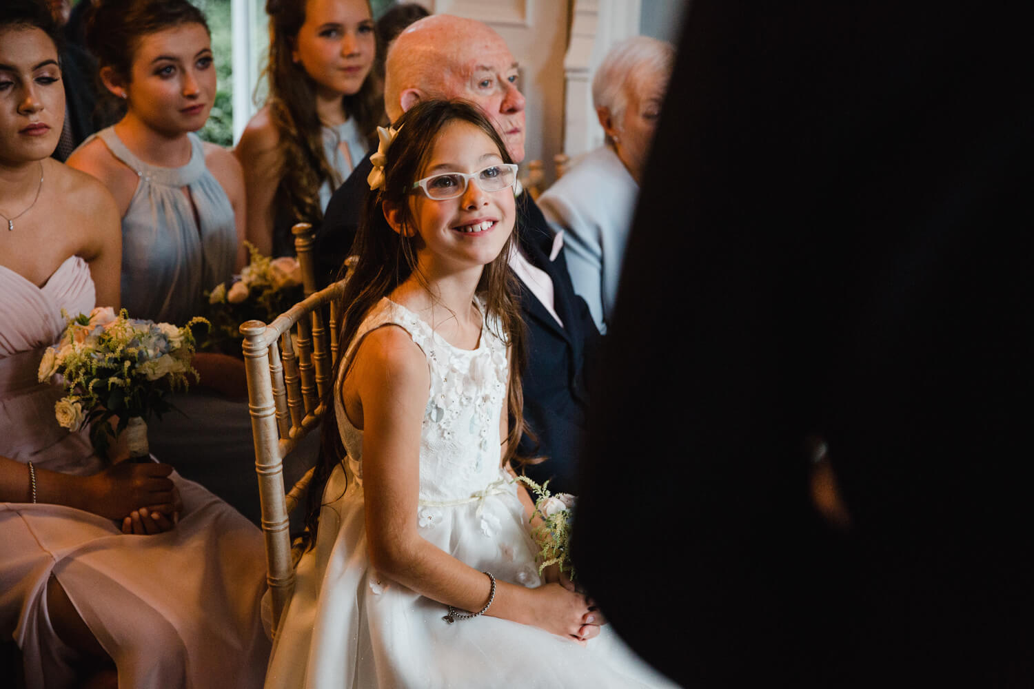 close up macro lens photograph of flower girl looking at bride and groom in foreground