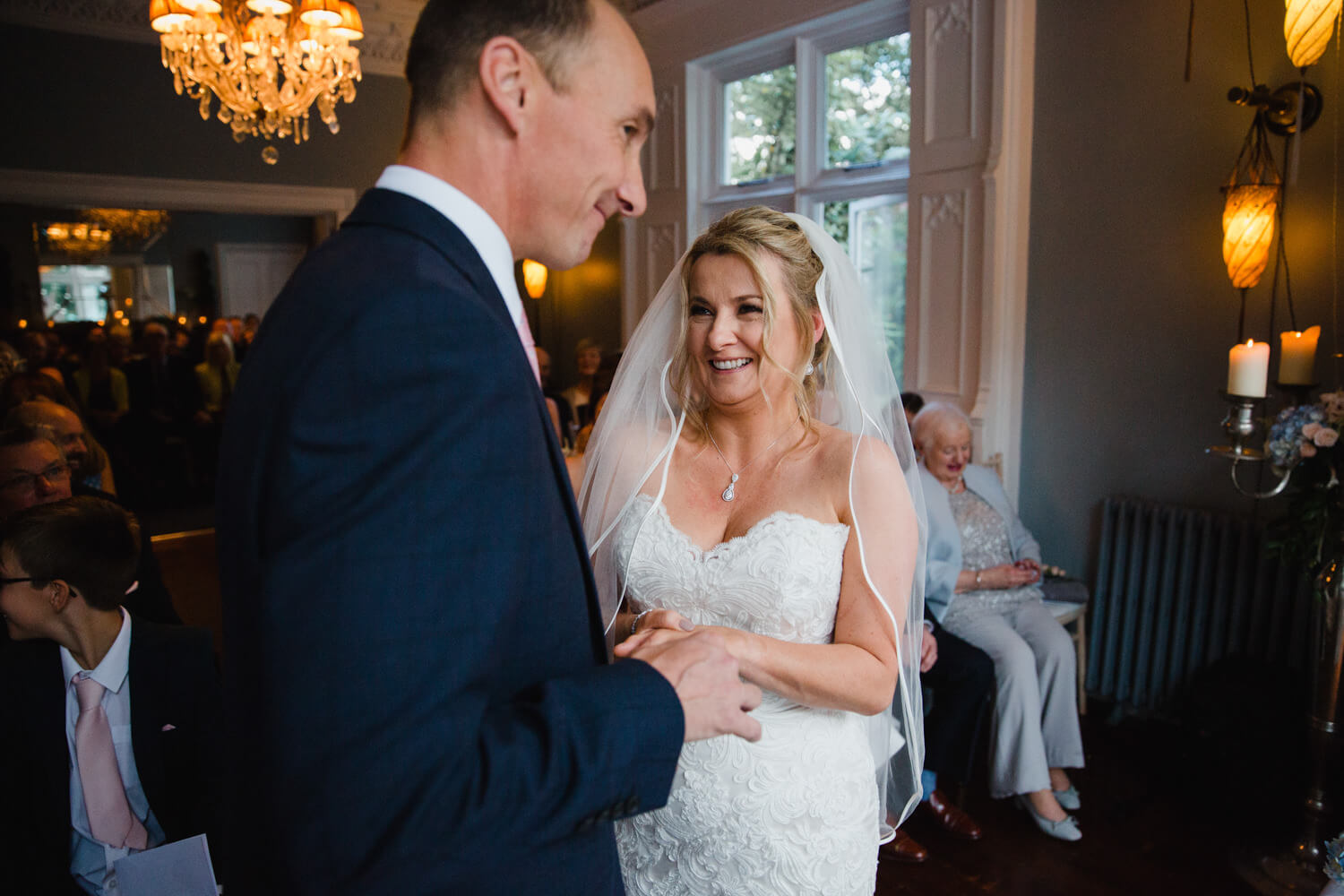 newly married couple exchanging wedding rings at didsbury house hotel