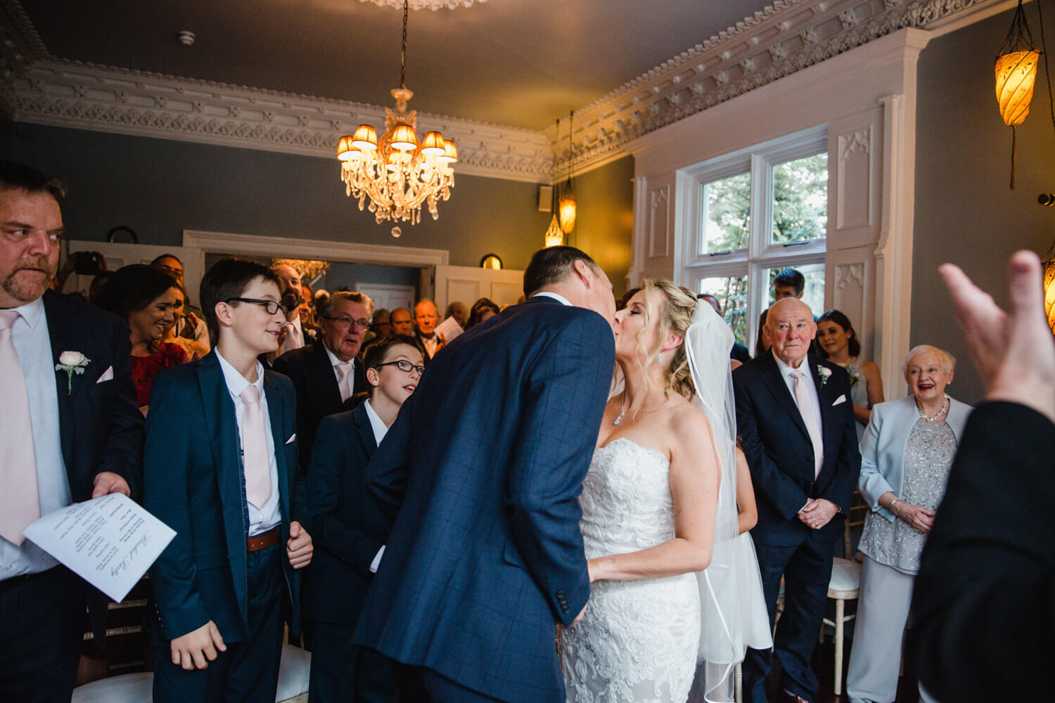 wide angle lens photograph of first kiss at didsbury house hotel as family and friends all celebrate