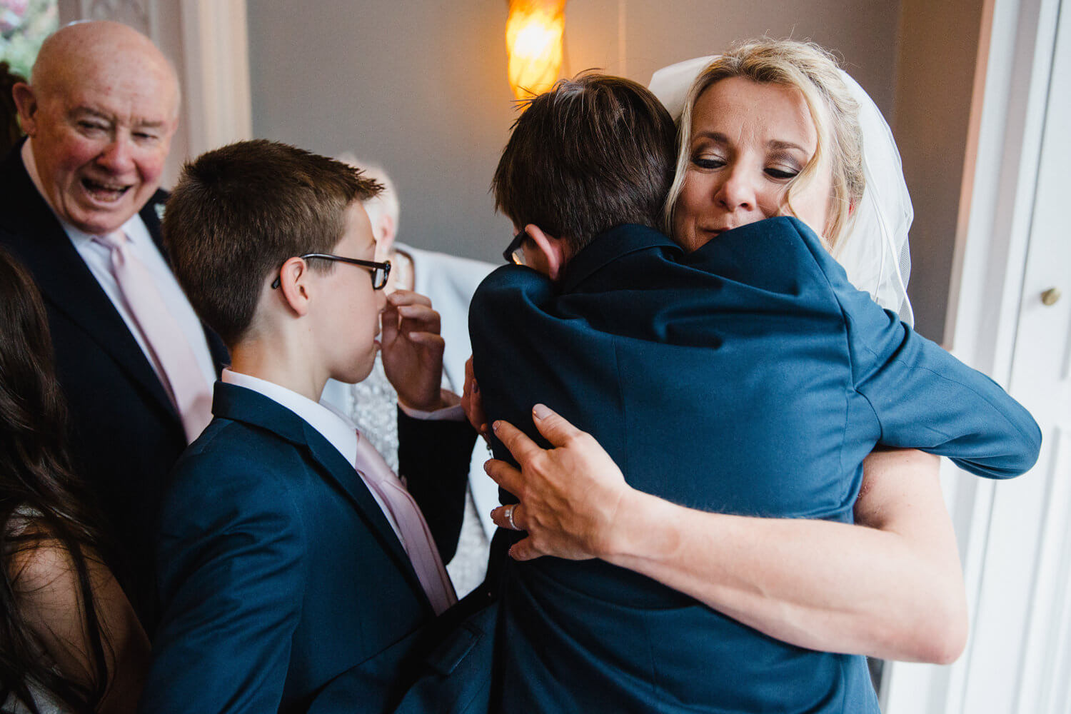 page boys hug bride in foreground as grandfather laughs in background of didsbury house hotel wedding photography