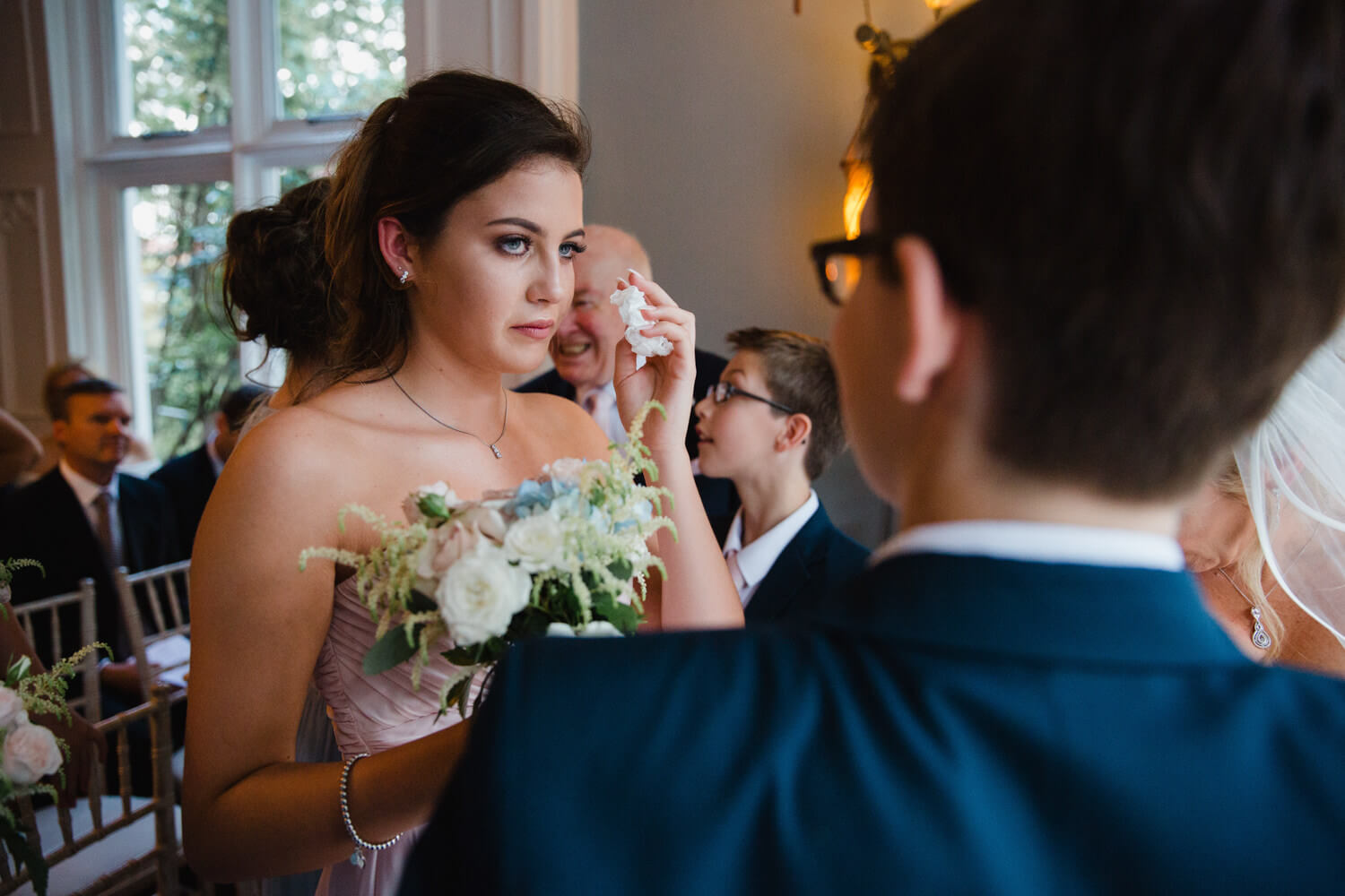 bridesmaid wipes away tear with tissue