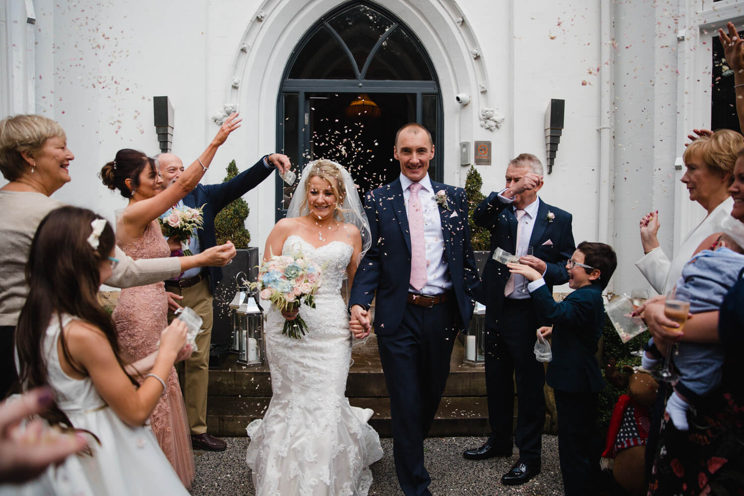 bride and groom showered with confetti in doorway of didsbury house hotel