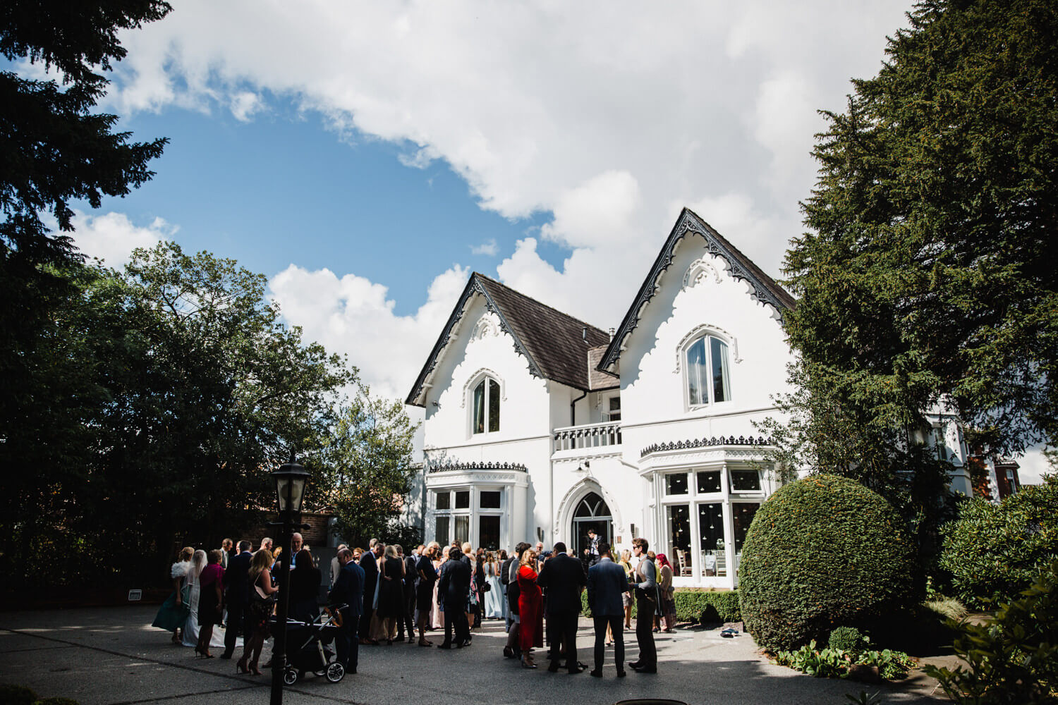 wide angle lens photograph of wedding party outside didsbury house hotel