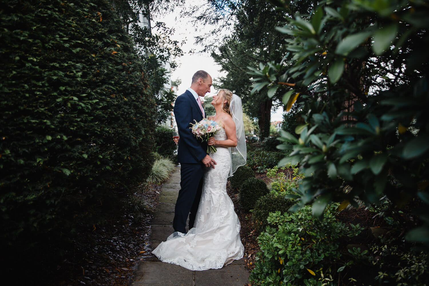 wide angle lends photograph of wedded couple in gardens