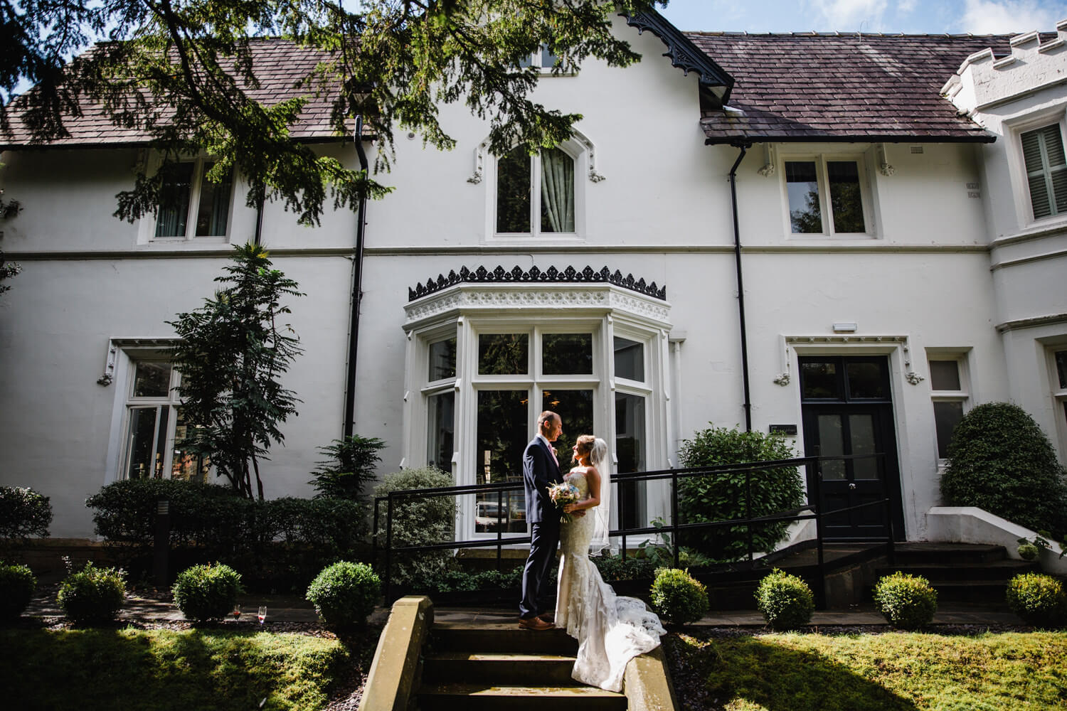 bride and groom posing in gardens of didsbury house hotel