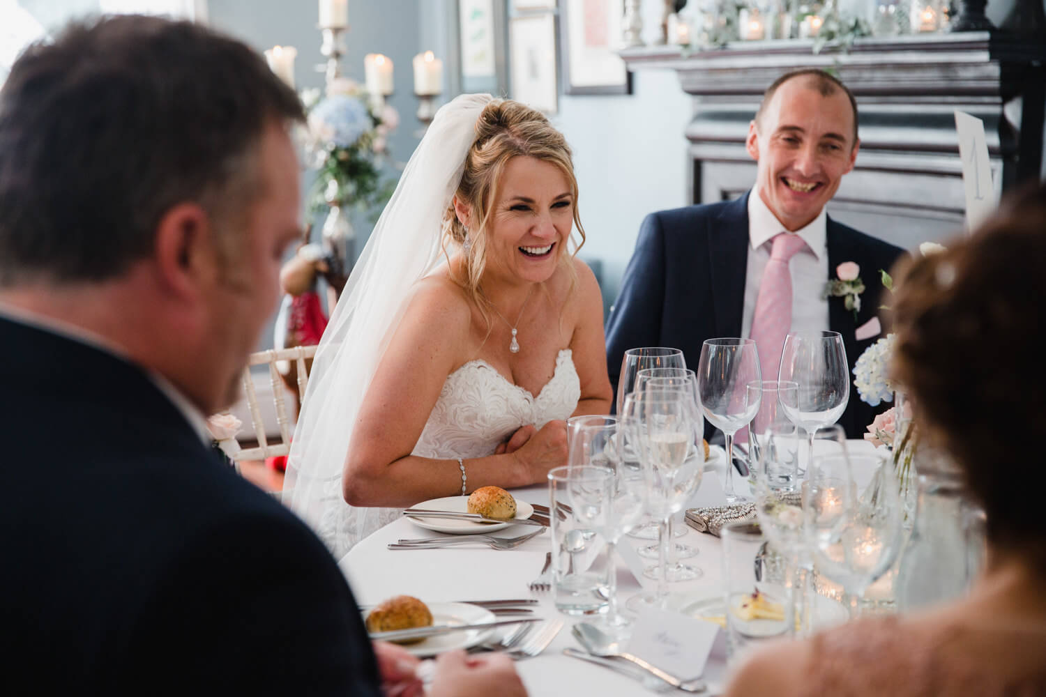 bride and groom laughing at jokes on table