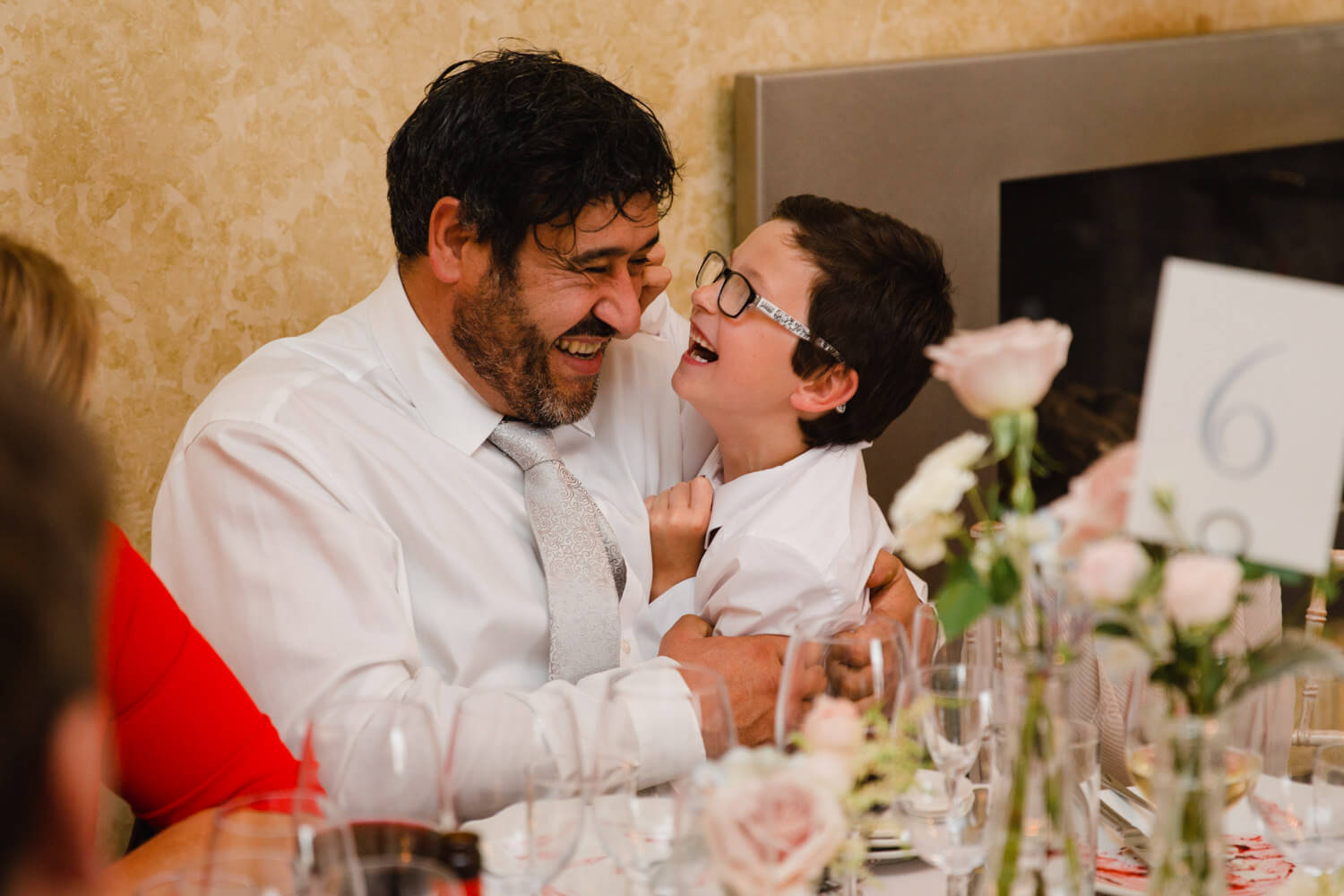 wedding guest holding page boy at table while laughing at each other