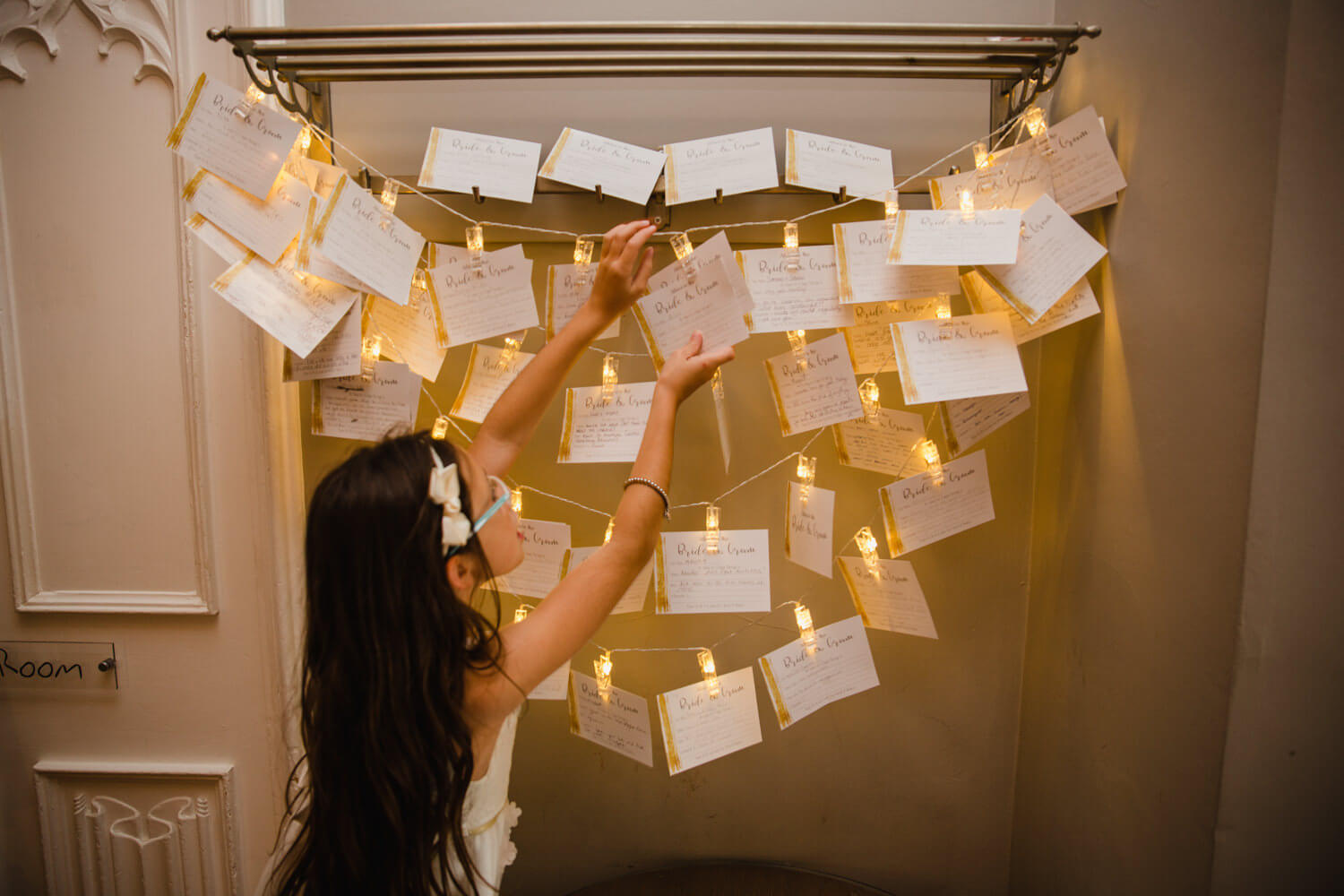 flower girl pinning wedding invitation to string in hallway