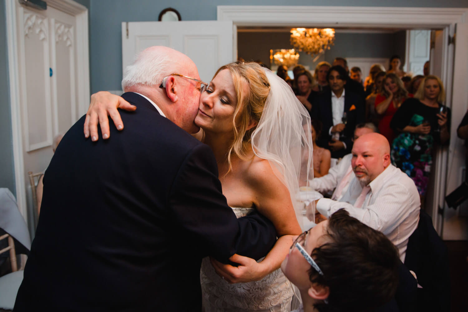 bride hugs father with wedding party looking on in background