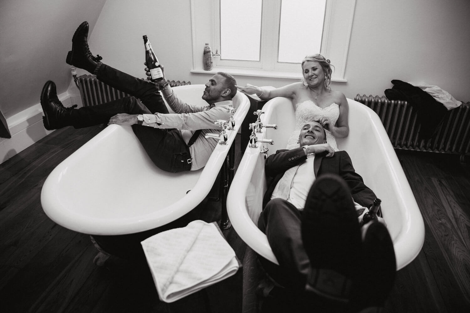 black and white photograph of bride and groom in bathtubs at didsbury house hotel