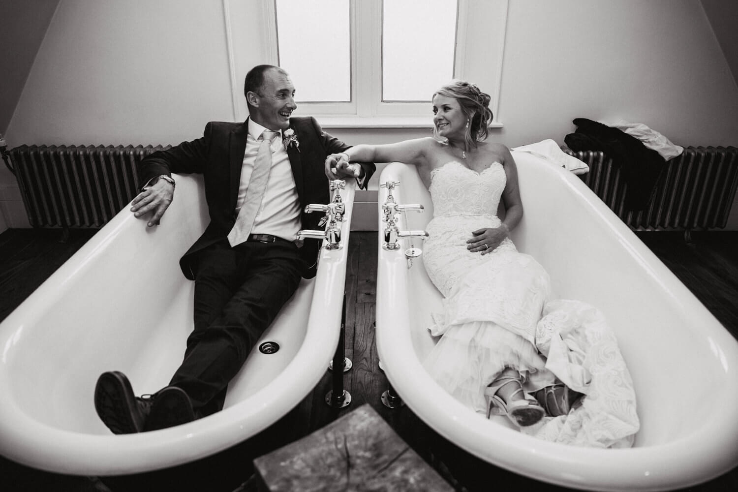 newlyweds pose for black and white photograph in bathtubs at didsbury house hotel