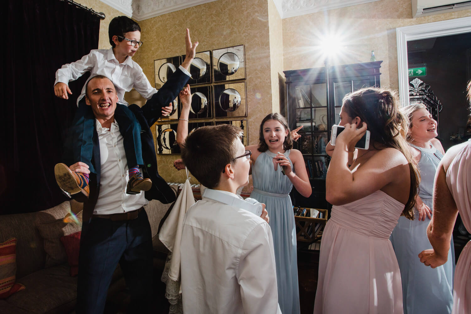 camera flash adds contrast to groom dancing with bridesmaids and page boy
