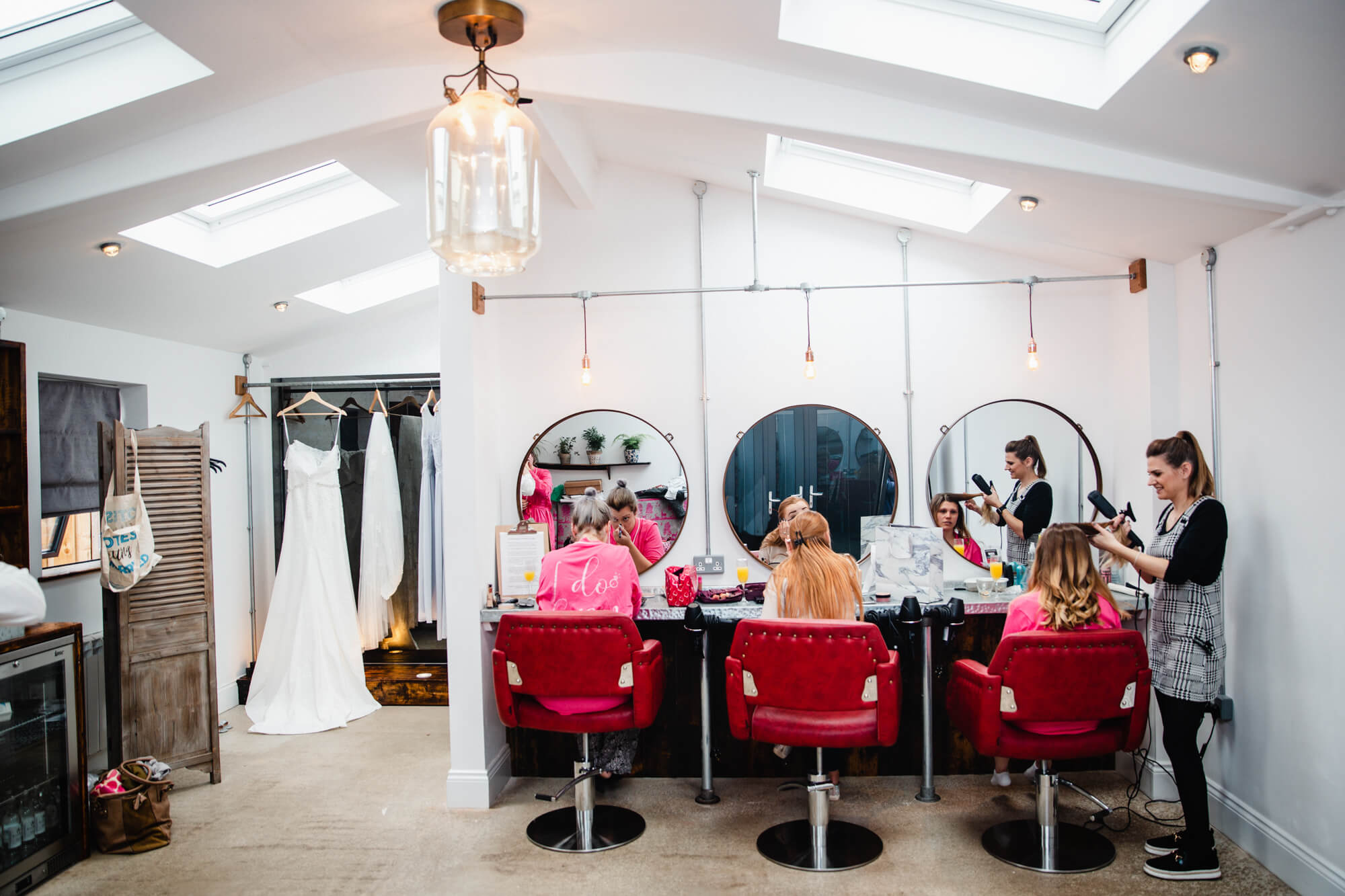 wide angle lens photograph inside owen house wedding barn bridal suite as bridesmaids apply make-up