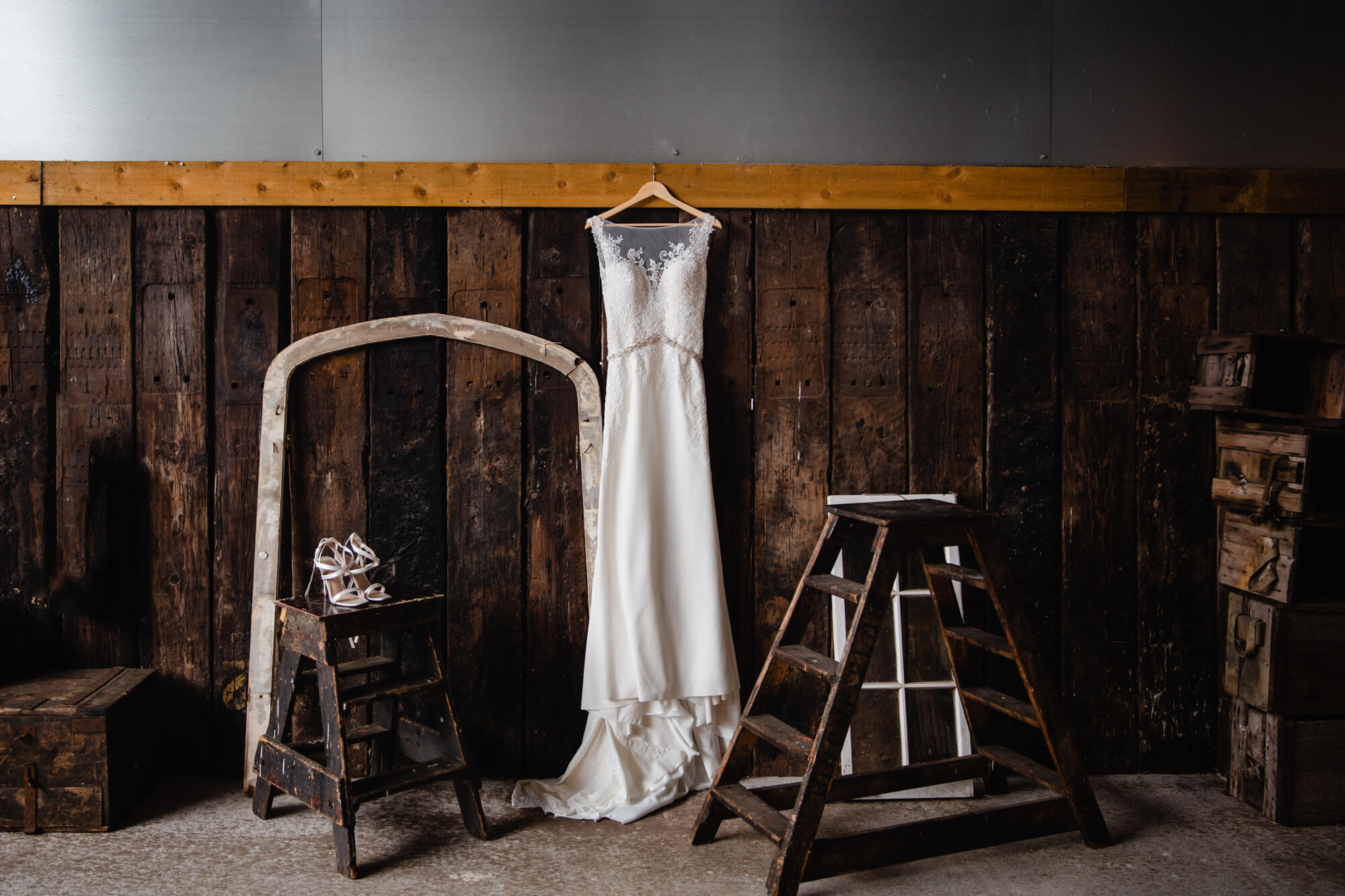 wedding dress and bridal shoes hanging from barn-door wall