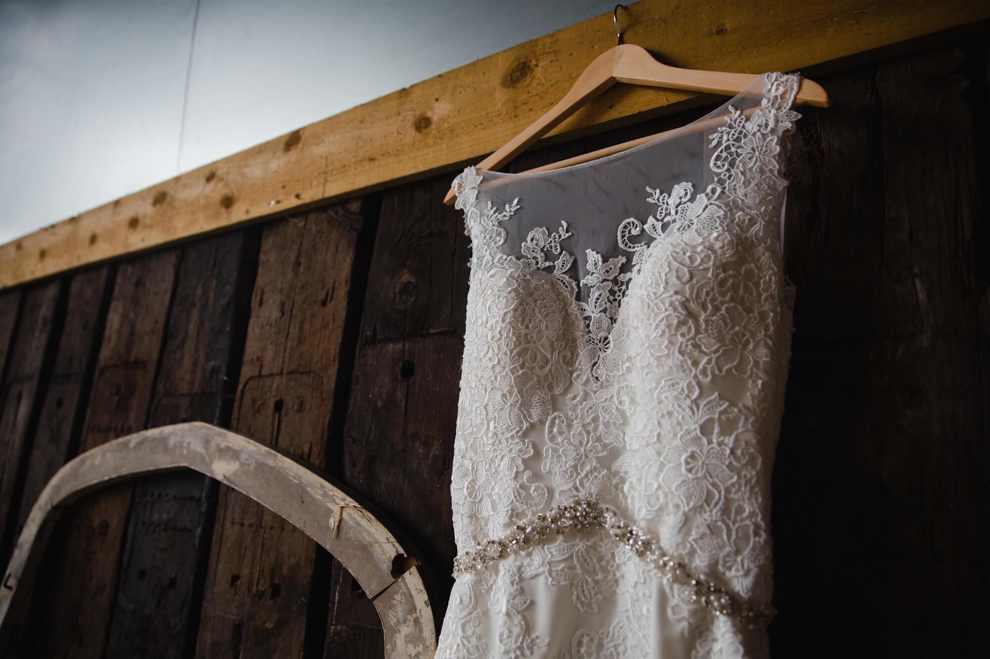 macro lens detail photograph of wedding dress on wall of barn