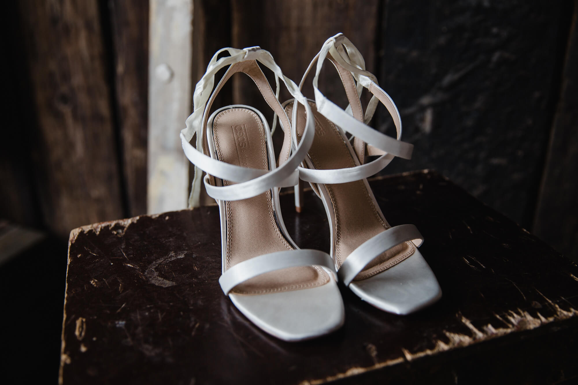 bridal shoes in wedding barn to contrast against brown backdrop