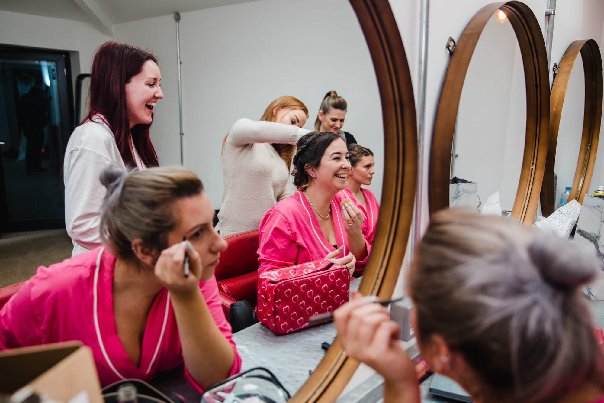 bridesmaids apply make-up in mirrors of bridal suite at owen house wedding barn