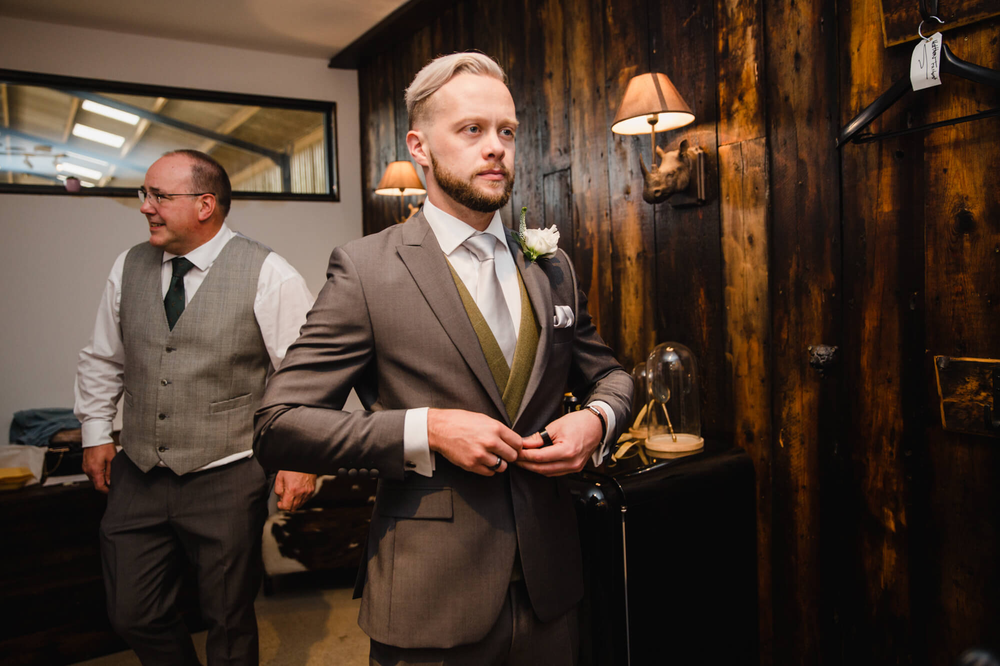 groom fastening whitfield and ward suit buttons before attaching flowers to suit lapel