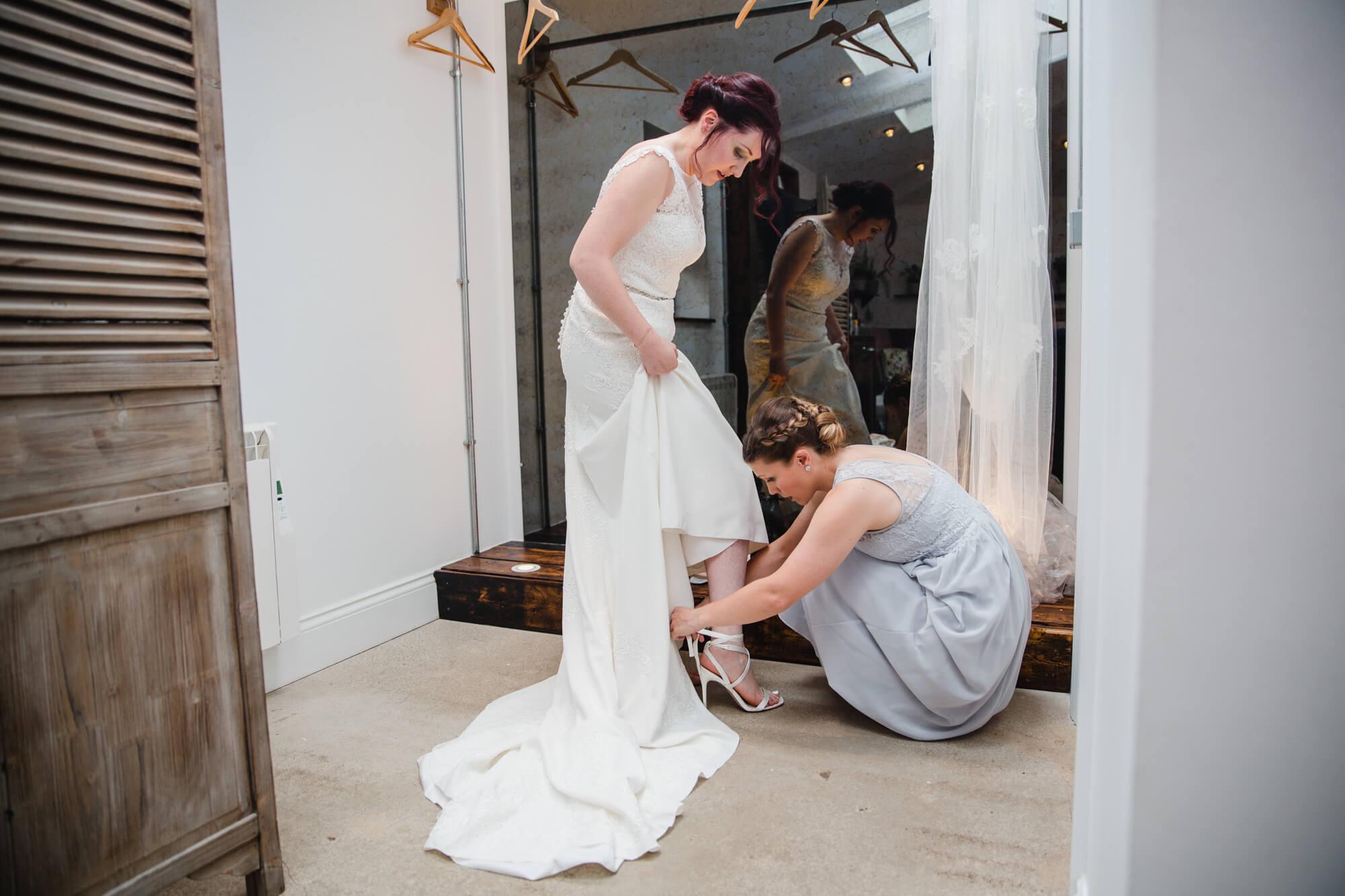 bridesmaid helping bride into wedding dress before ceremony begins