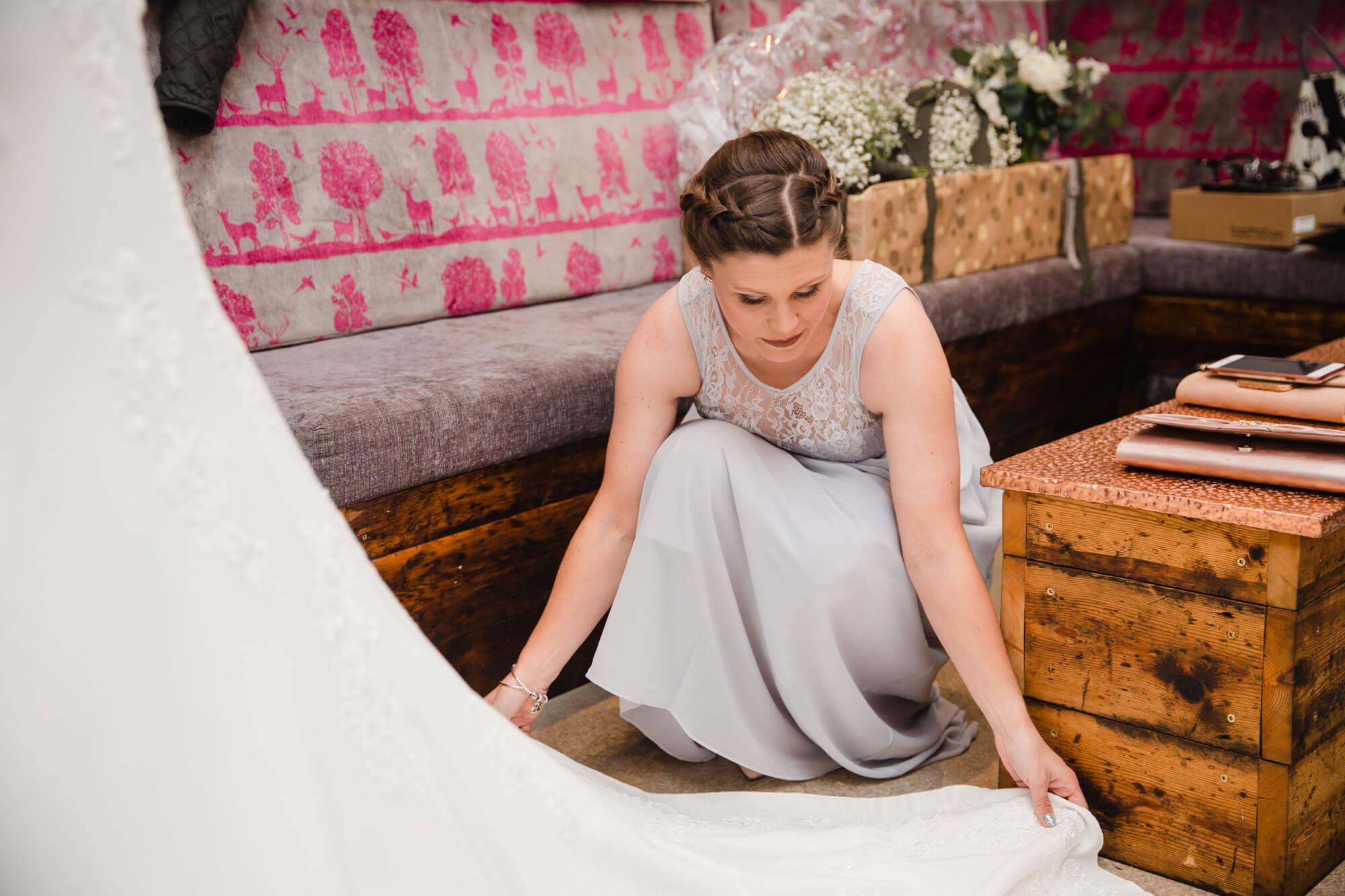candid relaxed photograph of bridesmaid arranging wedding dress at owen house wedding barn