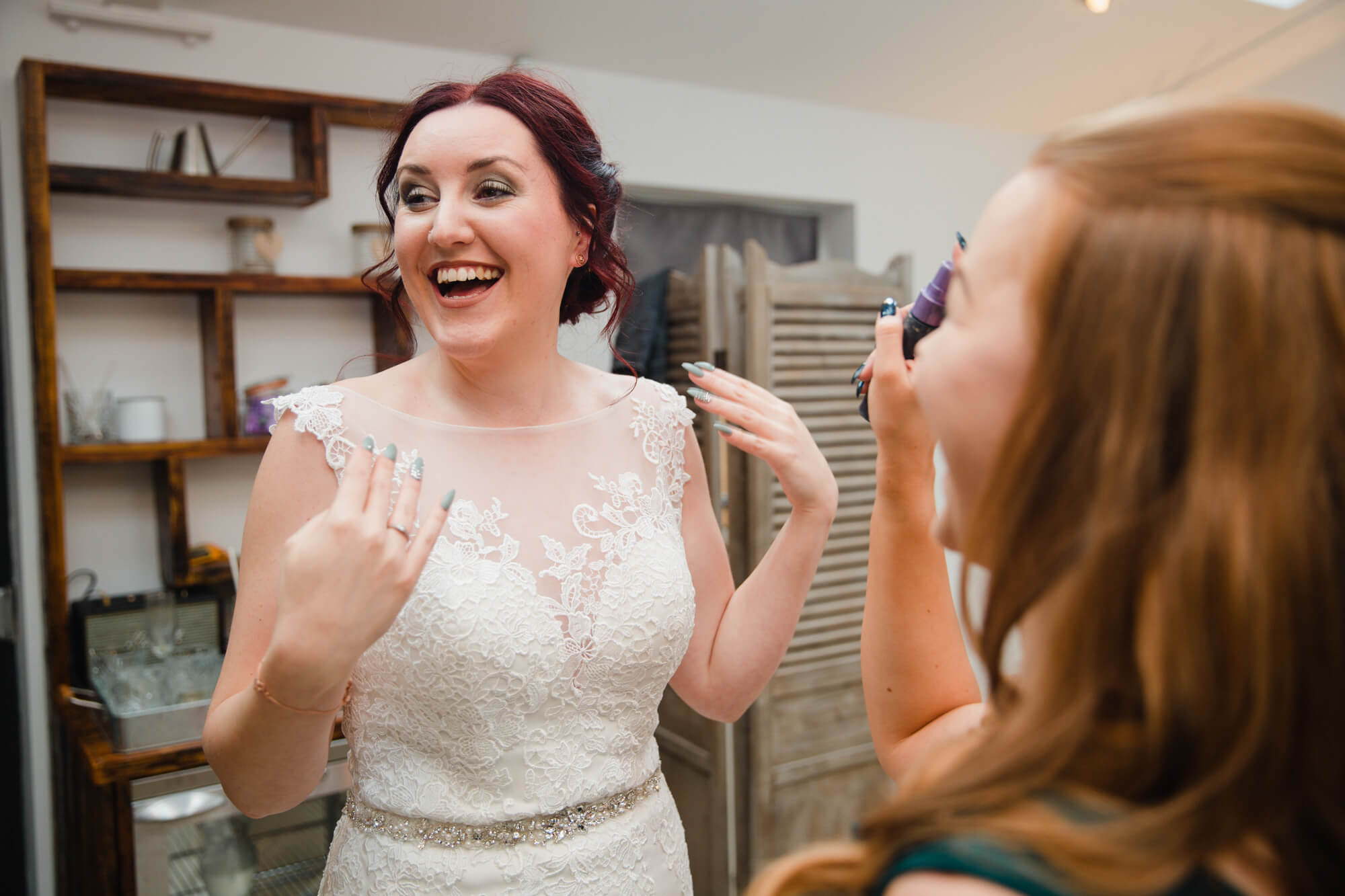 candid portrait photograph bride laughing with bridesmaids while putting on wedding dress before ceremony