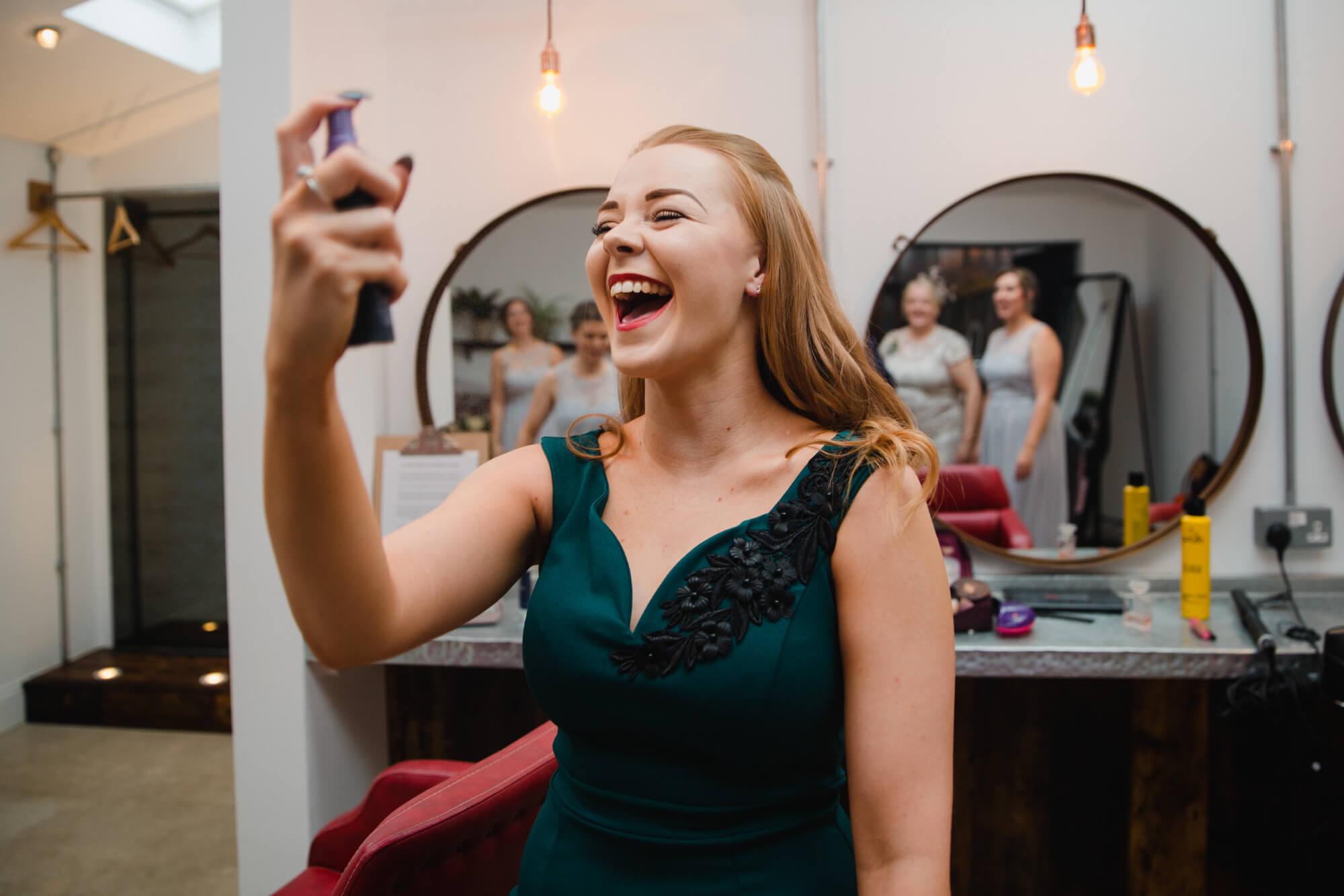 natural funny moment with bridesmaid spraying face as bridal party look on in the mirror