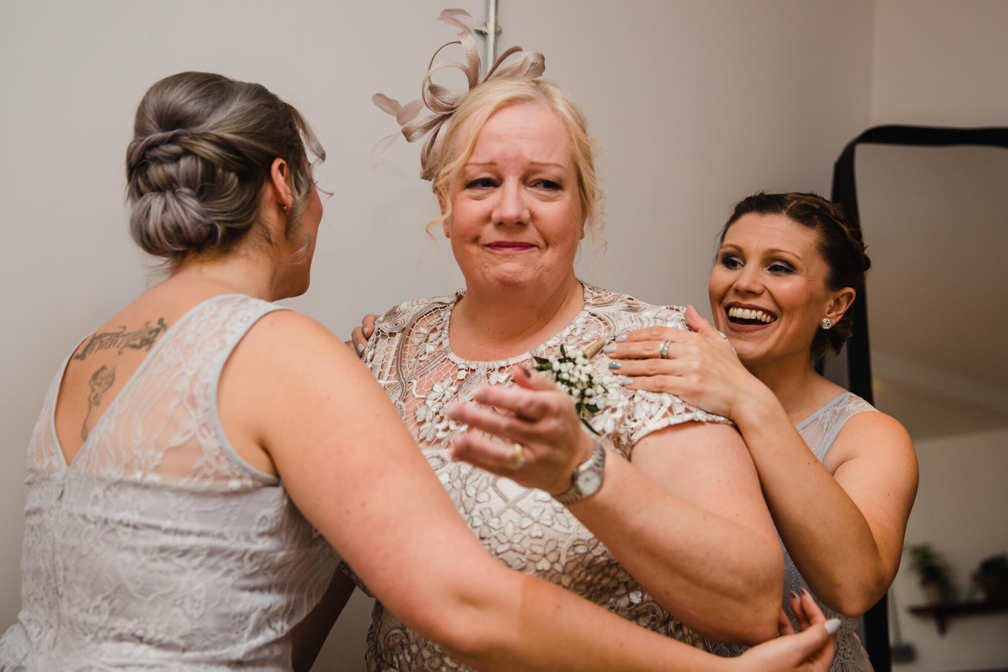 intimate moment as the mother of bride being comforted by bridesmaids