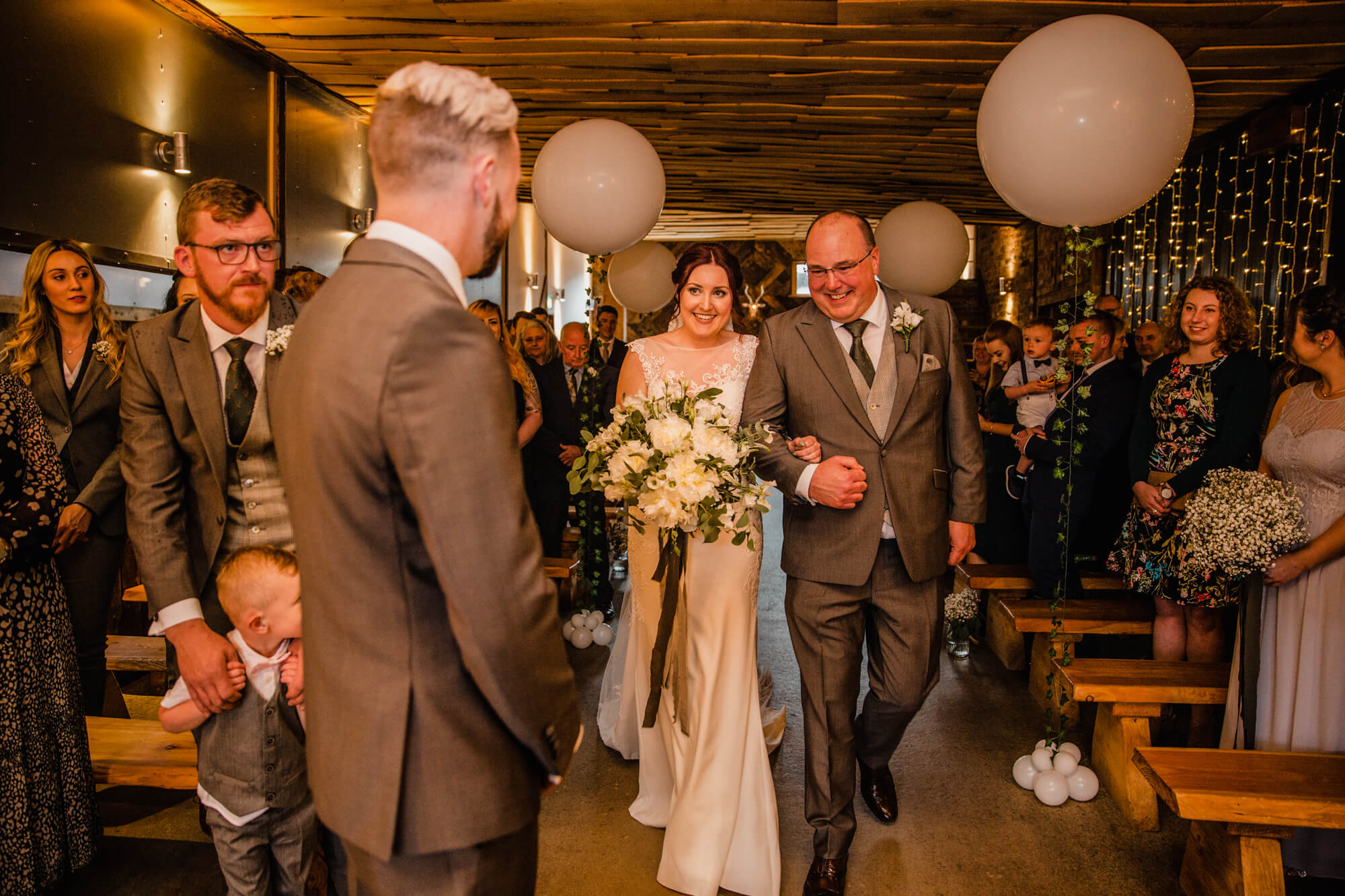 father of bride walks daughter down aisle to wedding processional as groom looks on in foreground