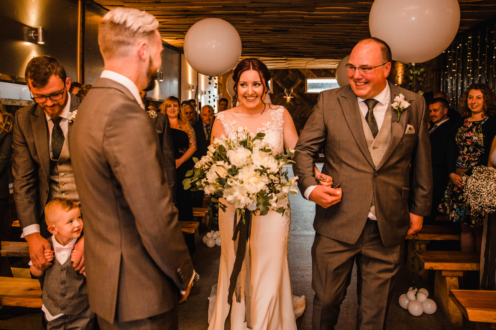 close up photograph of bride walking down aisle to be greeted by groom in forground