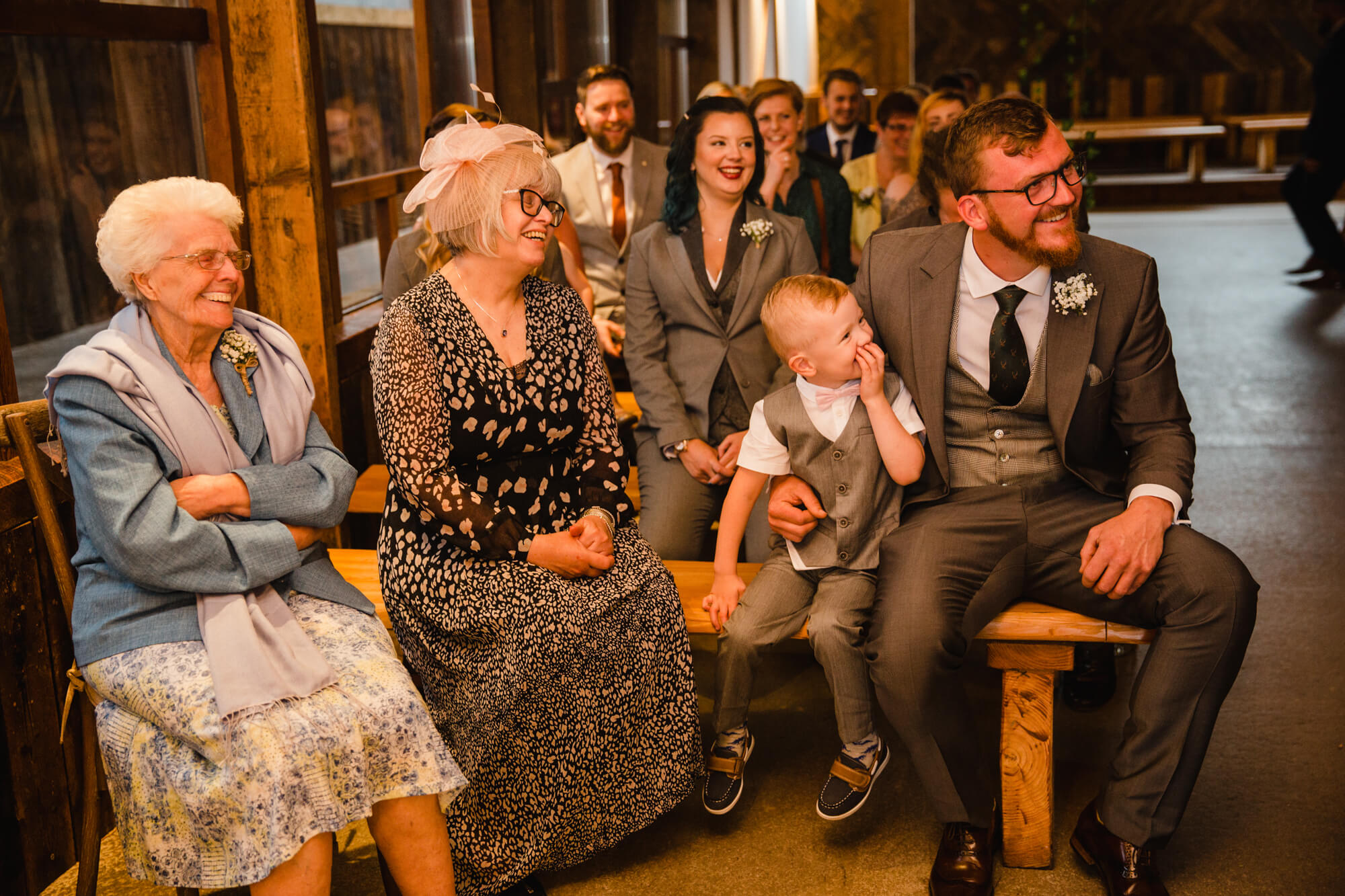 candid natural moment as grooms family watch wedding rings being exchanged by married couple