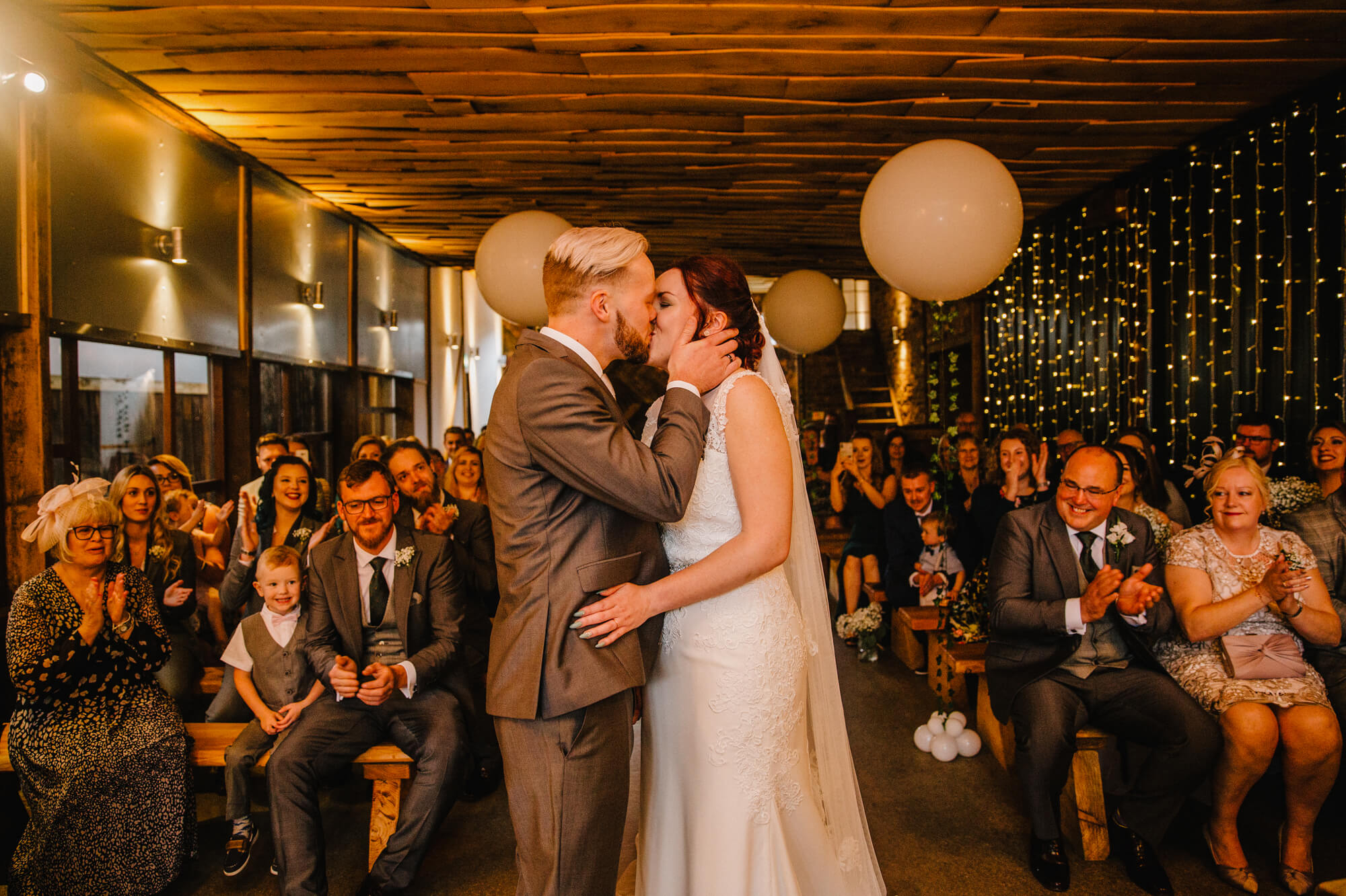 wedding service first kiss of newlyweds as bridal party celebrate