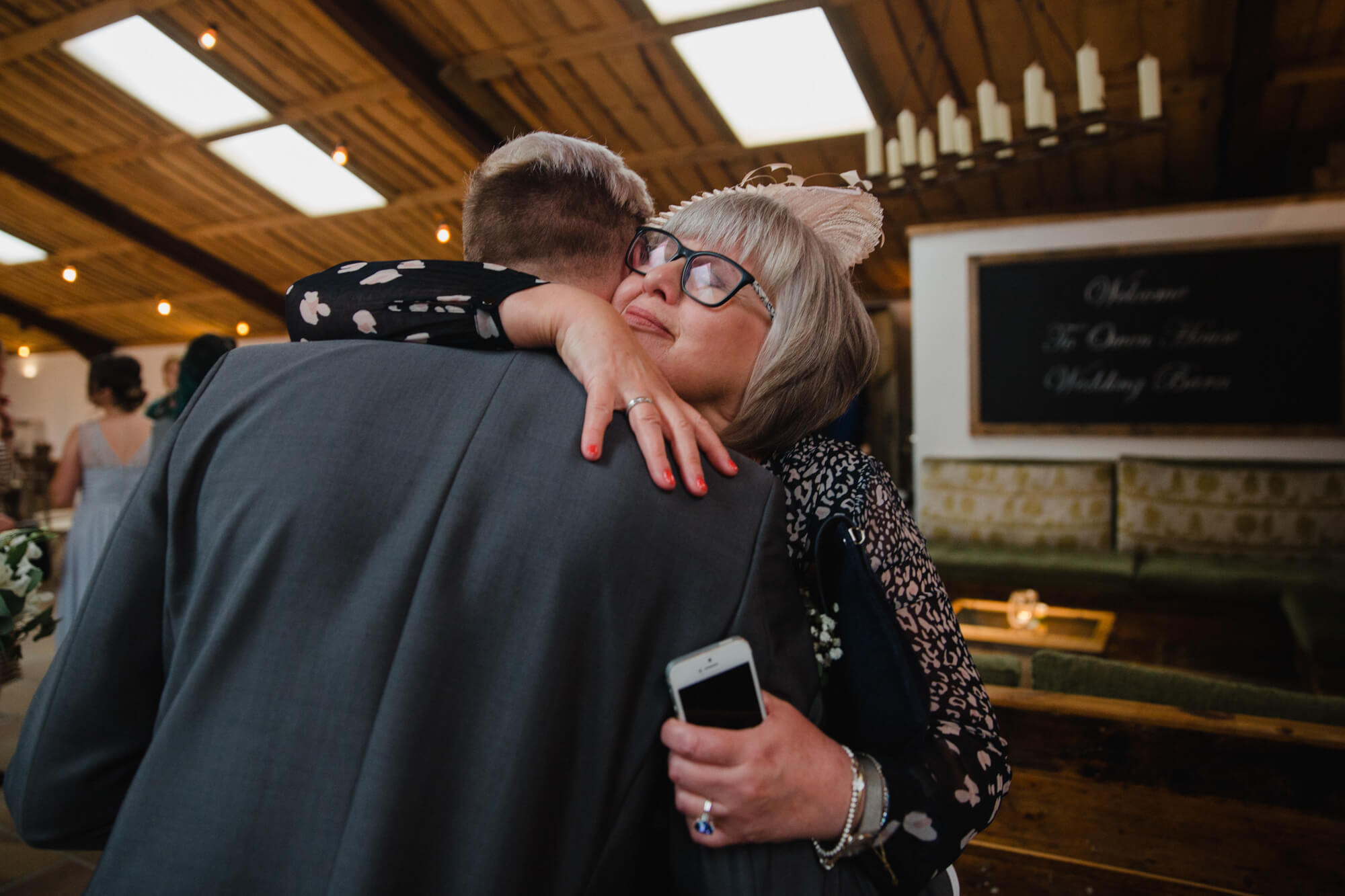 mother of groom shares intimate hug in candid photograph