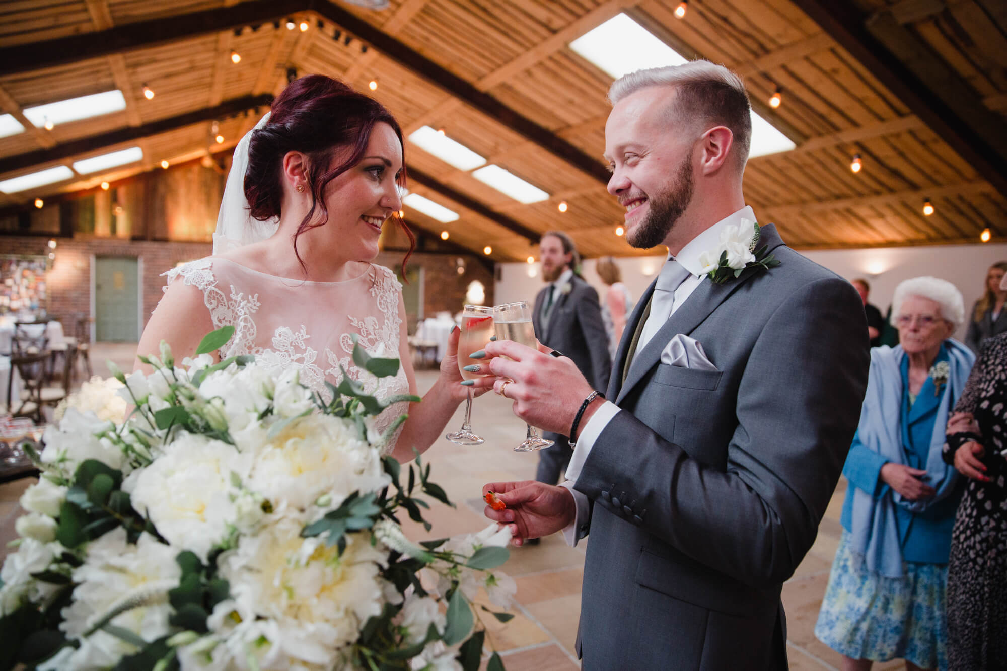bride and groom celebrate with a glass of champagne as service ends