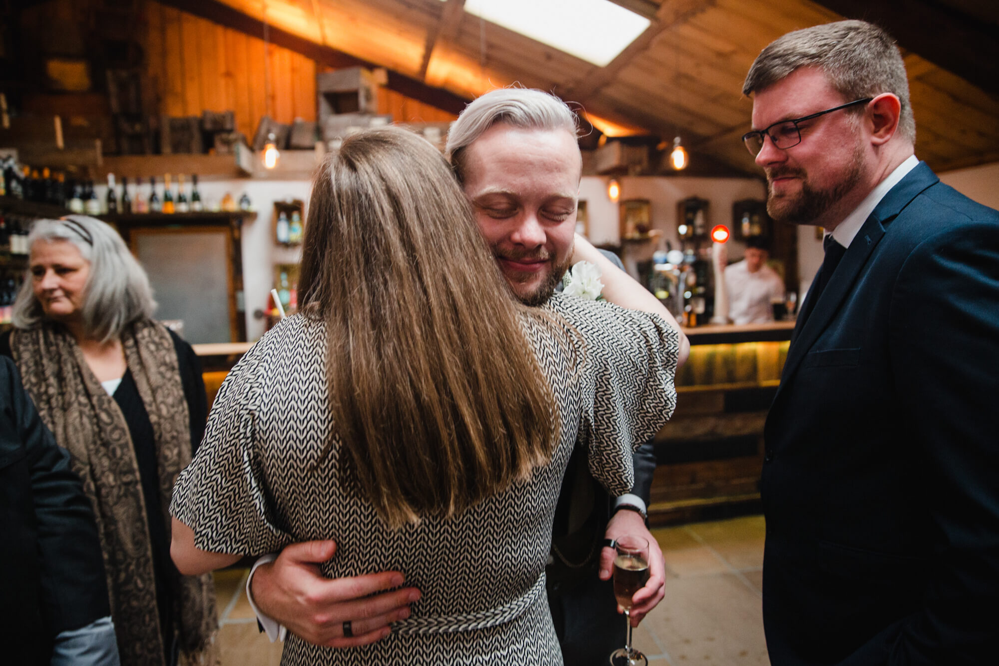 friend of newly married groom shares hug after wedding service