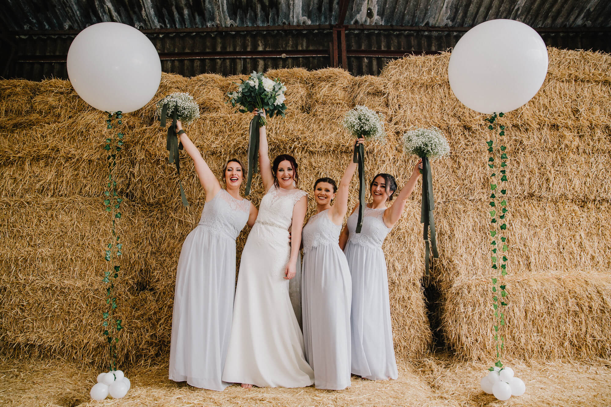 bride and bridal party hold bouquets in the air on top of hay bale backdrop for posed group photograph