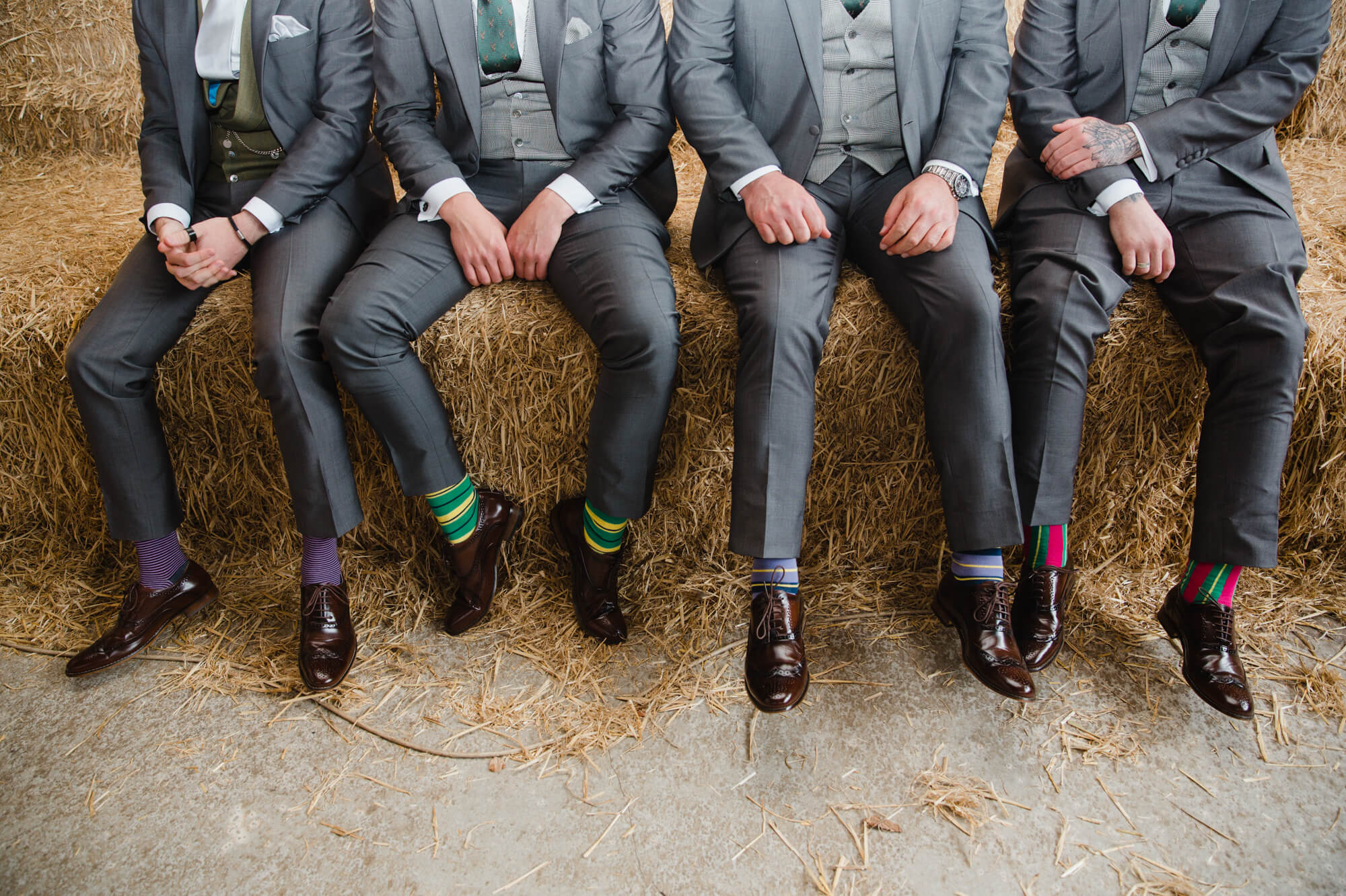 groomsmen posing on hay bale wearing striped coloured socks
