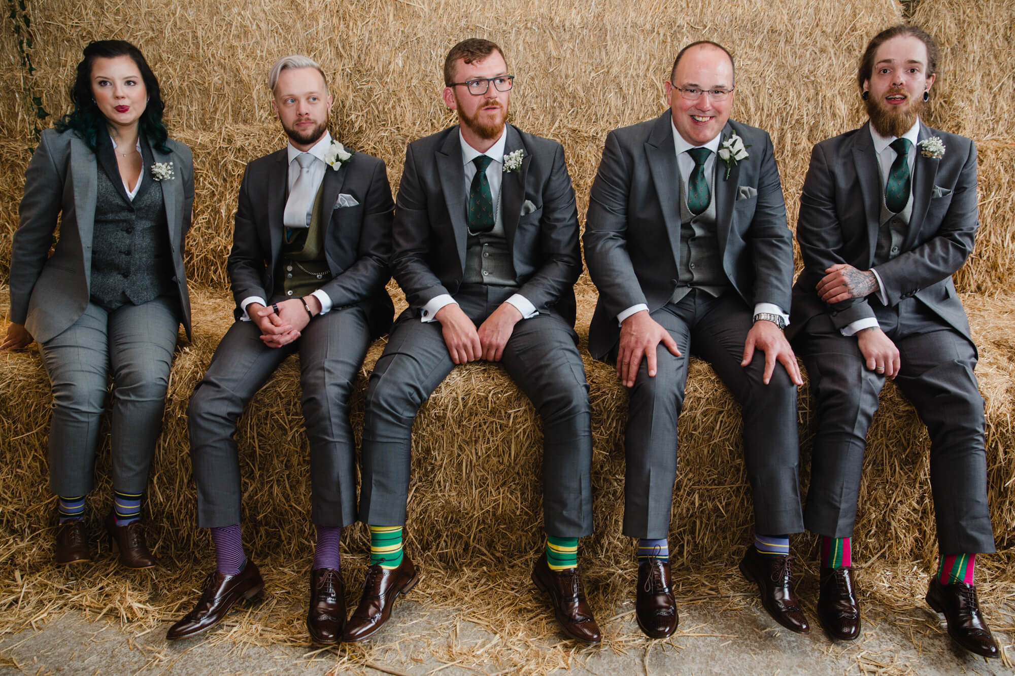 groomsmen sitting on hay bales in candid photography portrait