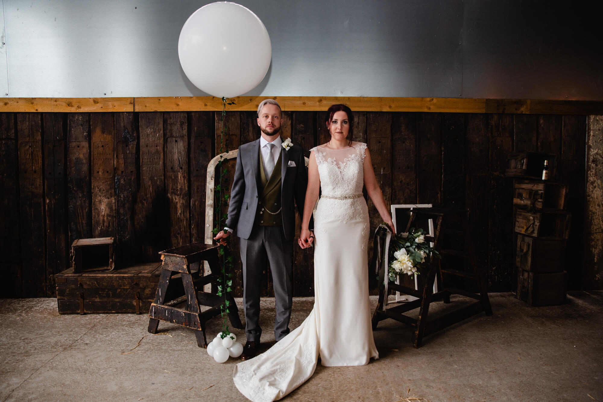 newlyweds pose looking at camera for portrait against barn wall backdrop