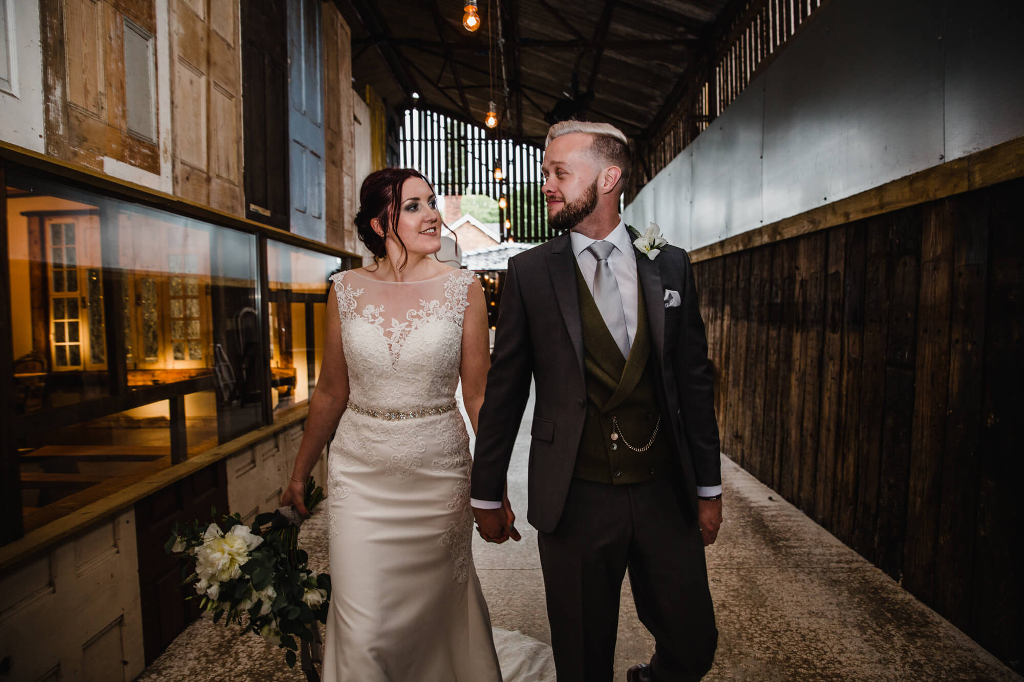 newly wedded couple walking toward camera for portrait flash photograph while holding bouquet against barn door