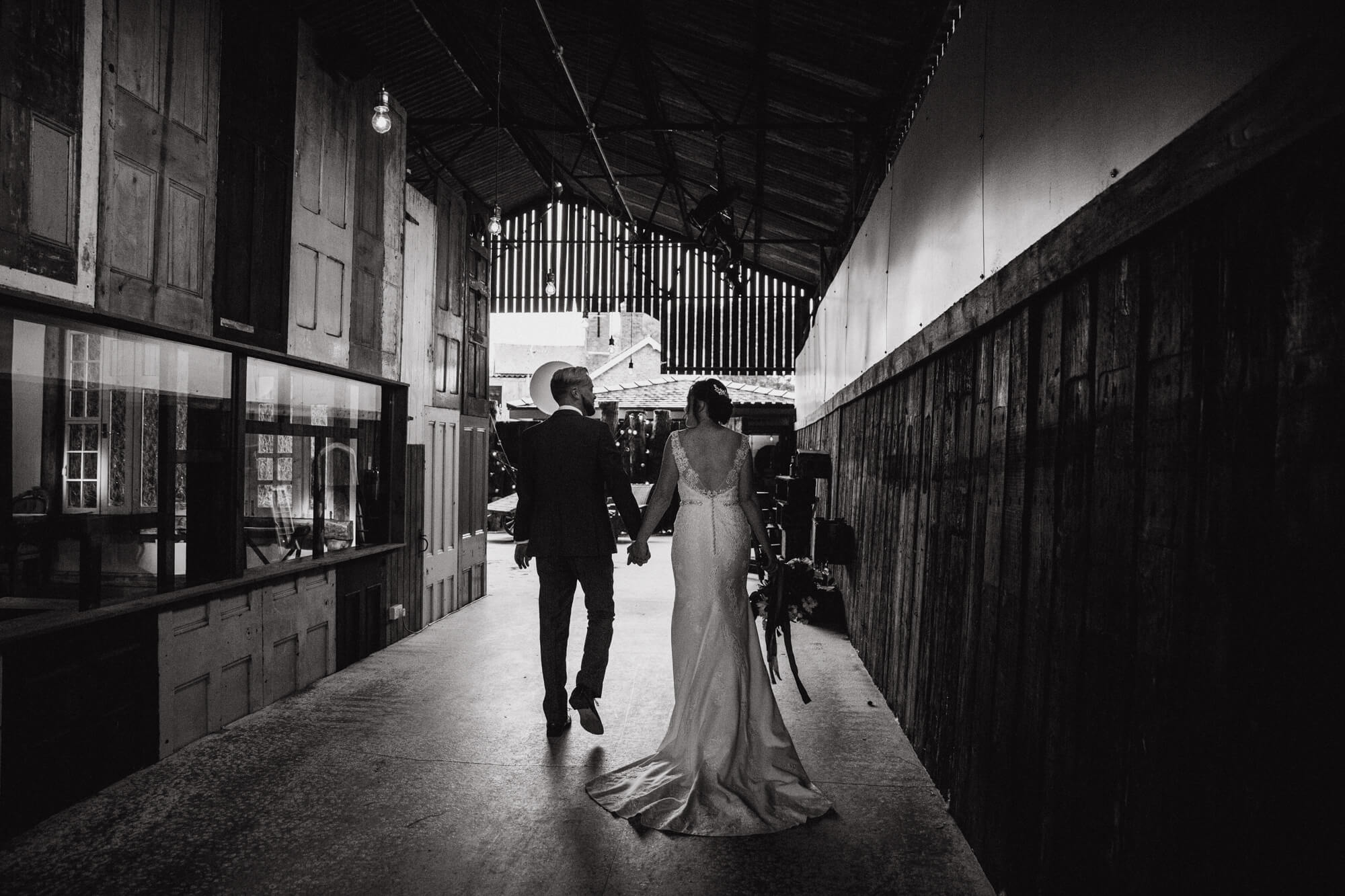 black and white photograph of bride and groom holding hands walking away from camera towards barn entrance hallway