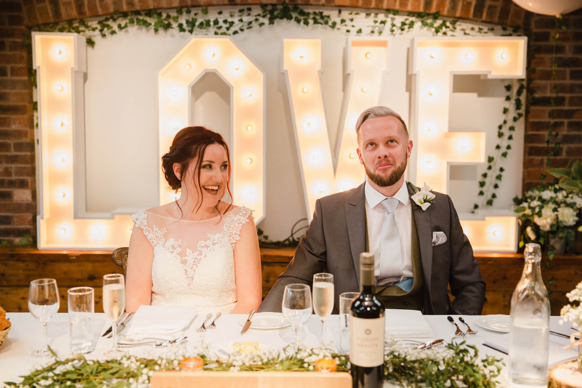 bride and groom sat at top table in foreground with LOVE letters in backdrop