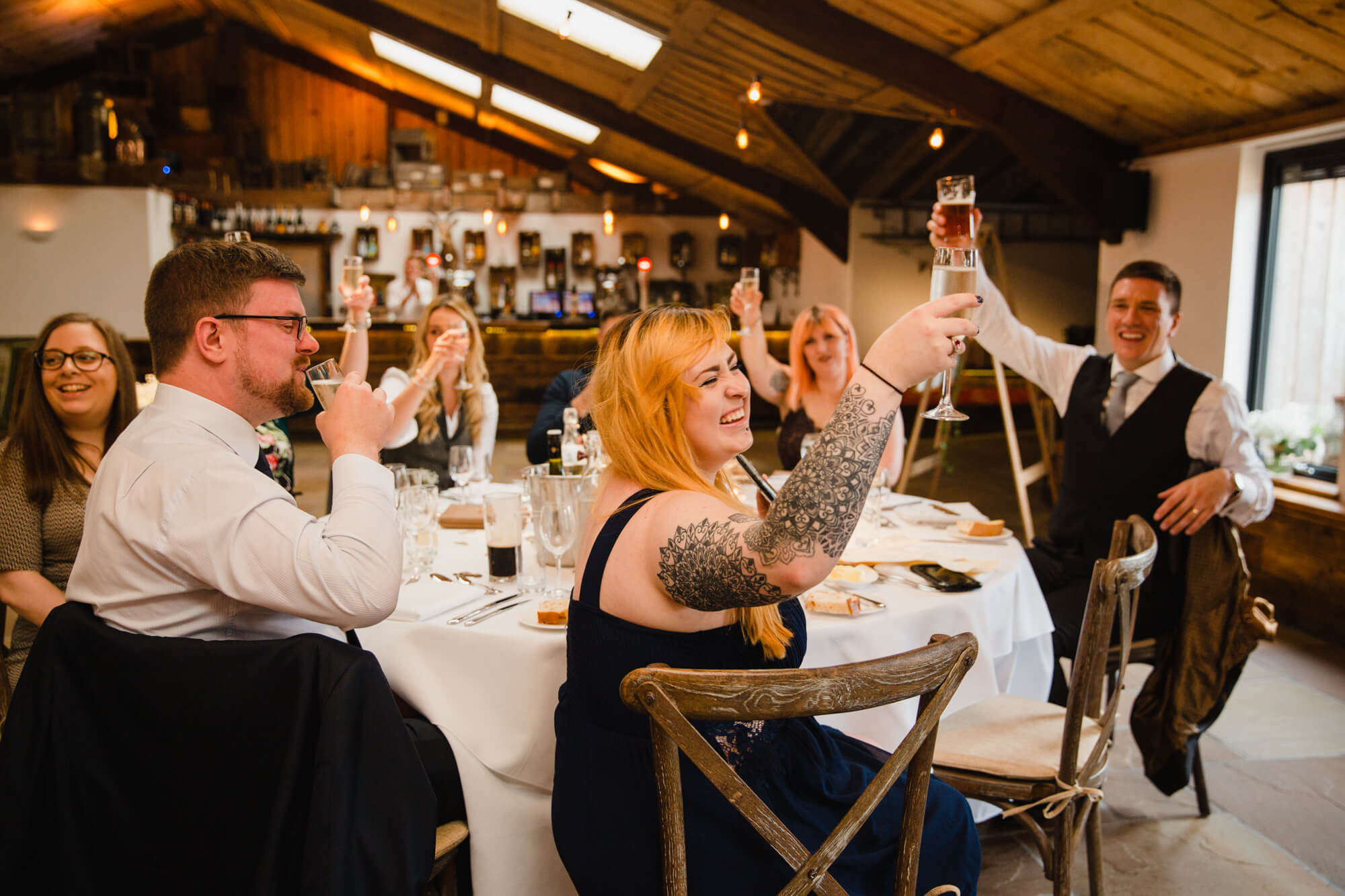 wedding guests raising glasses for toast to groom