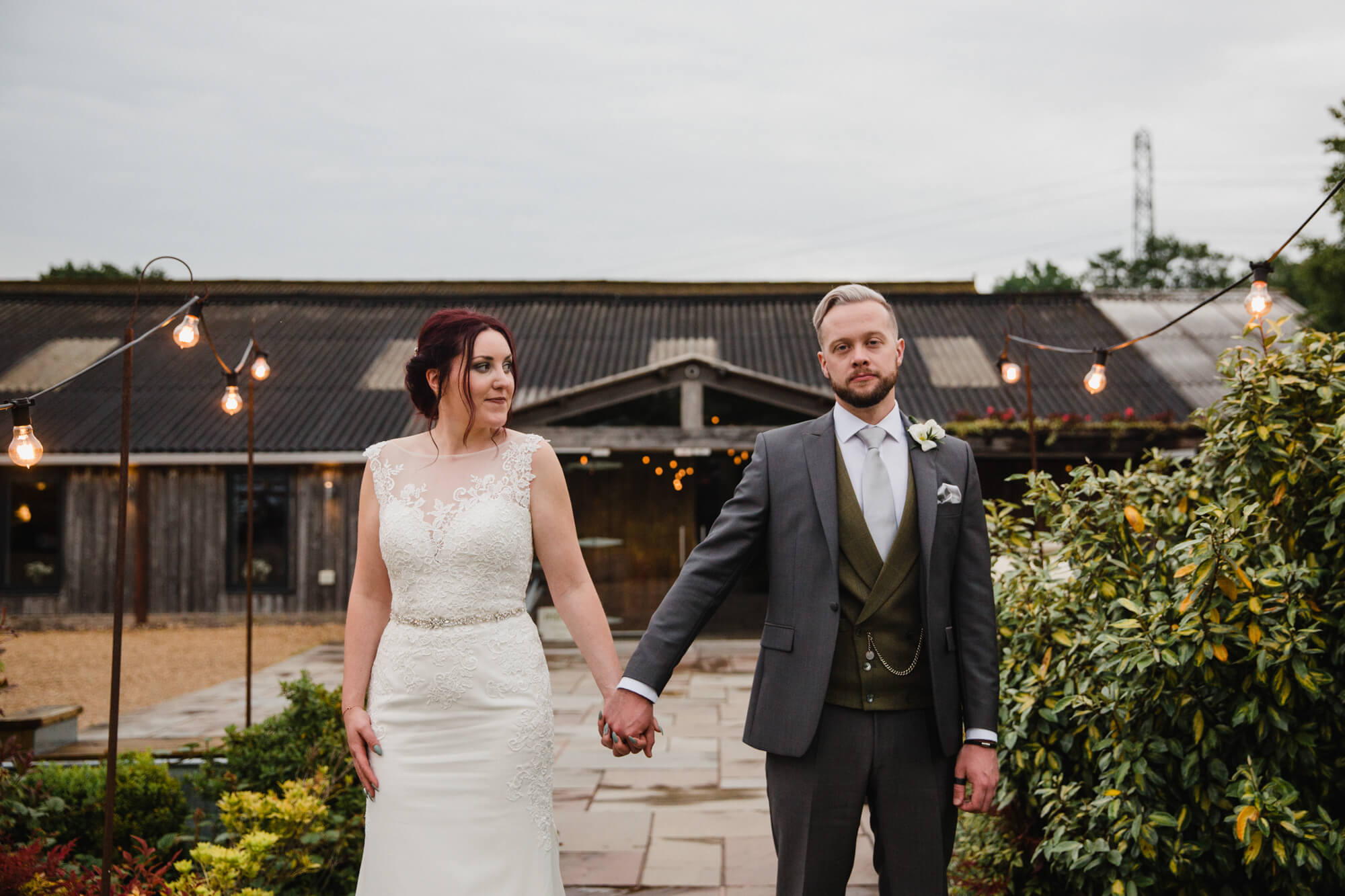 newlyweds hold hands while bride holds bouquet in front of barn doors at Owen House