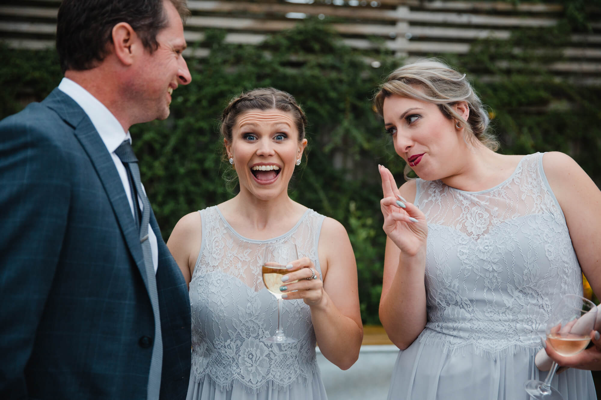 bridesmaids in wedding gowns having fun outside in barn gardens