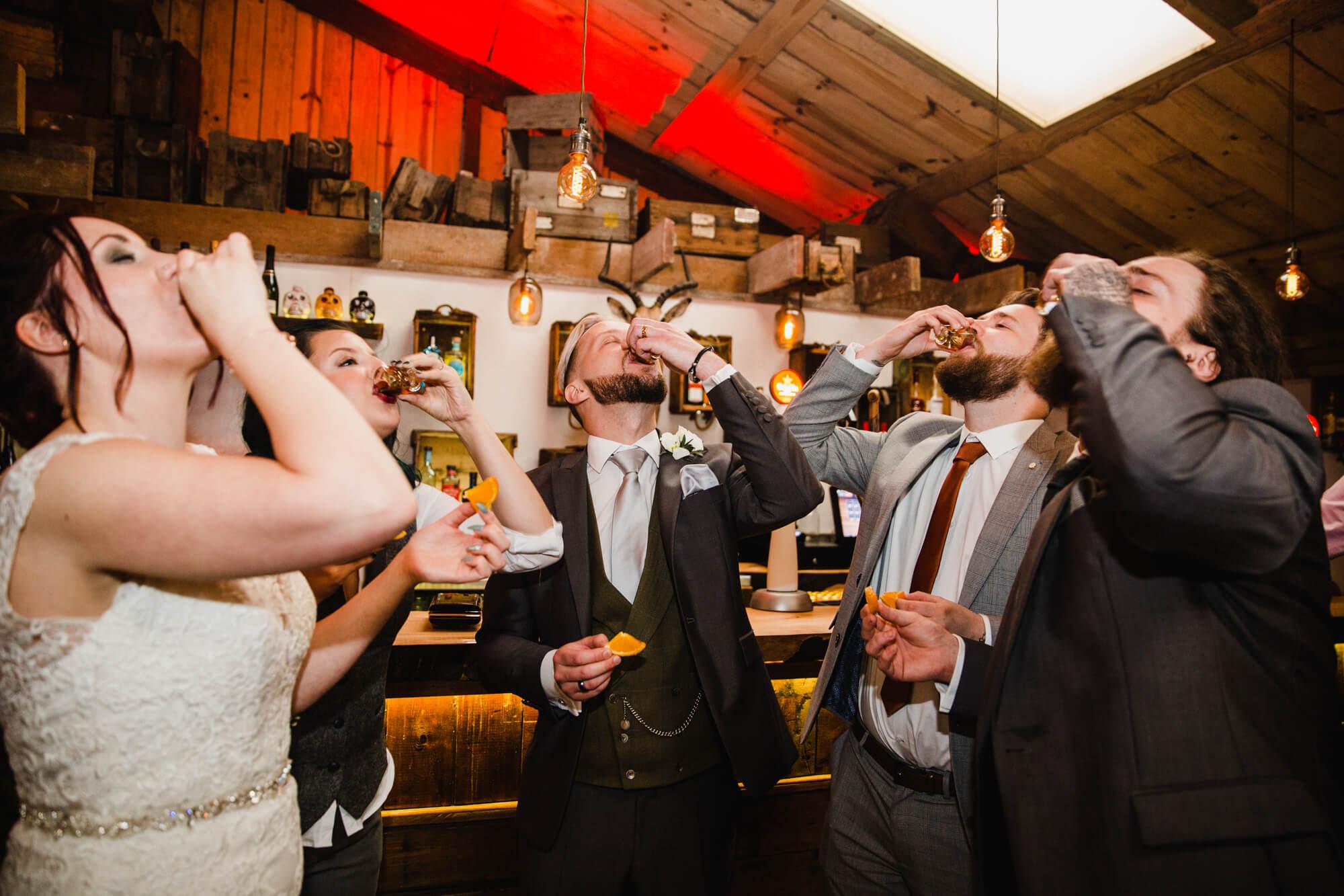 wedding party having shots at the bar
