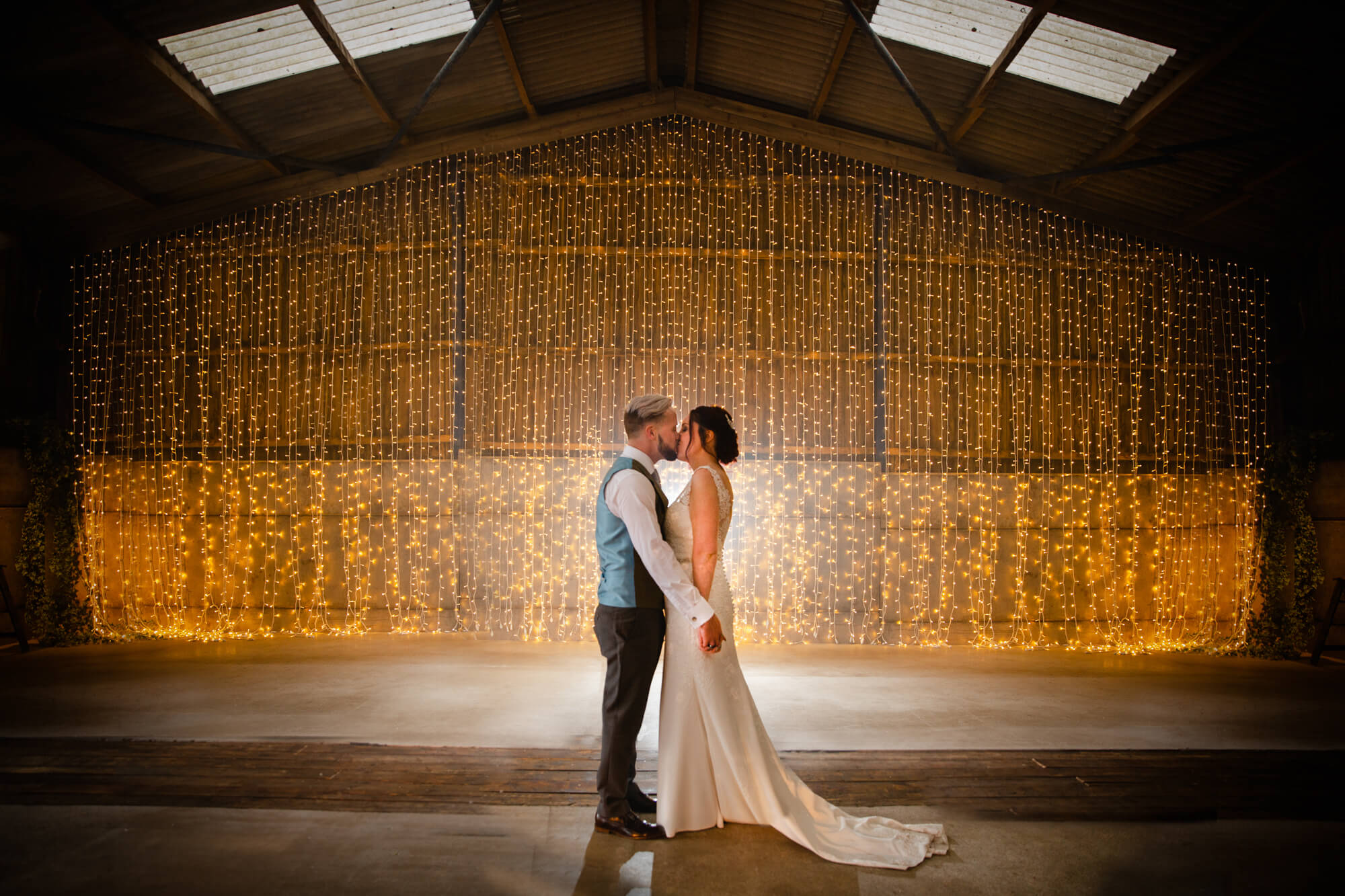 bride and groom kissing with light up barn door backdrop